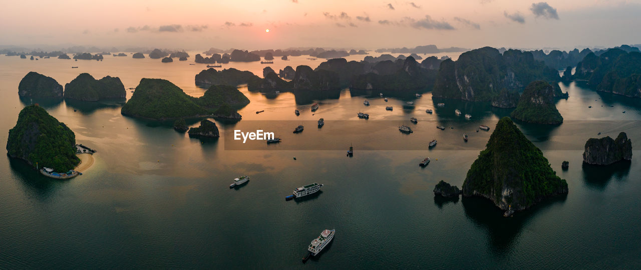 High angle view of rocks in sea during sunset