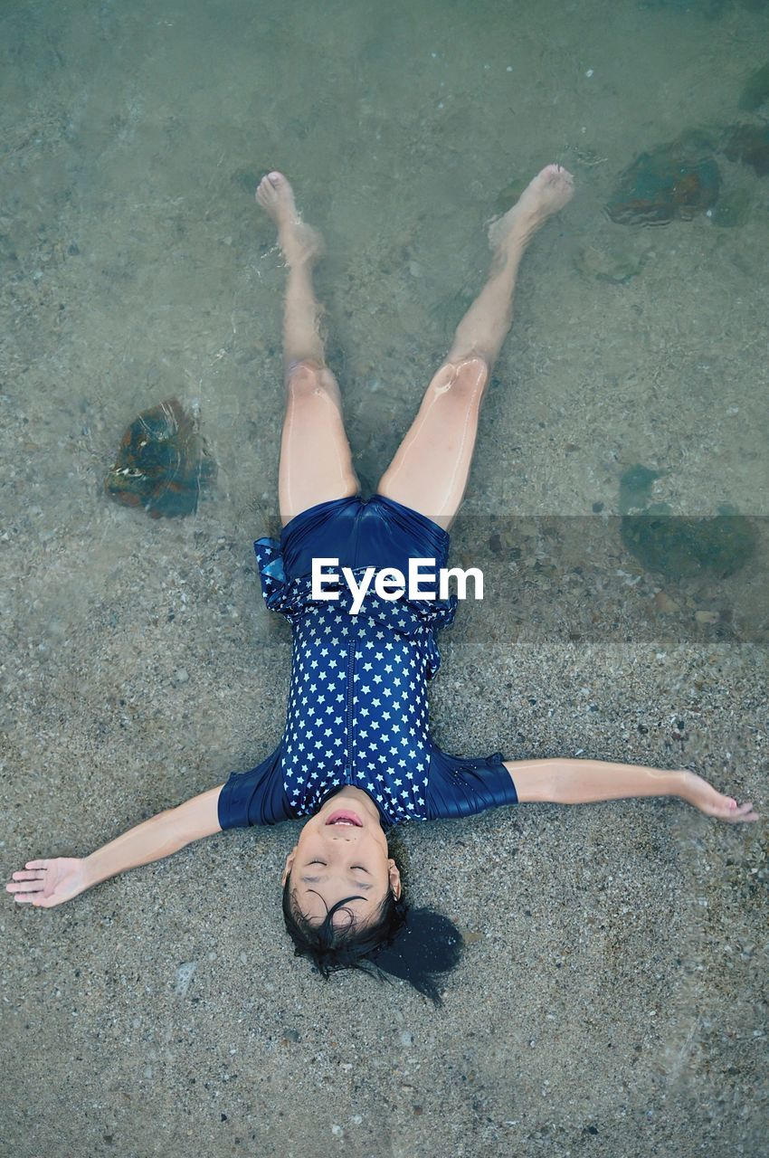 High angle view of girl lying at beach