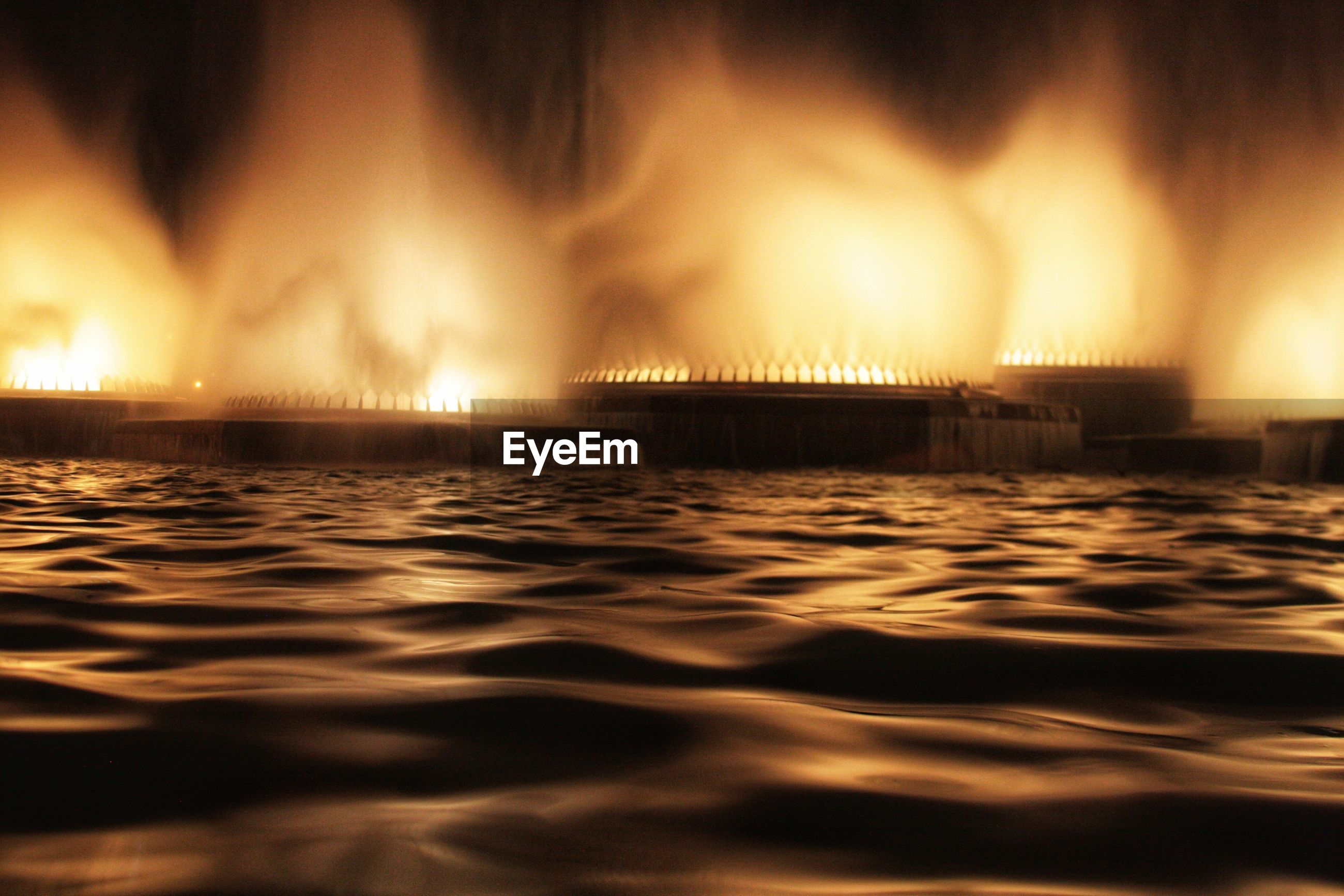 ILLUMINATED SEA AGAINST SKY AT NIGHT