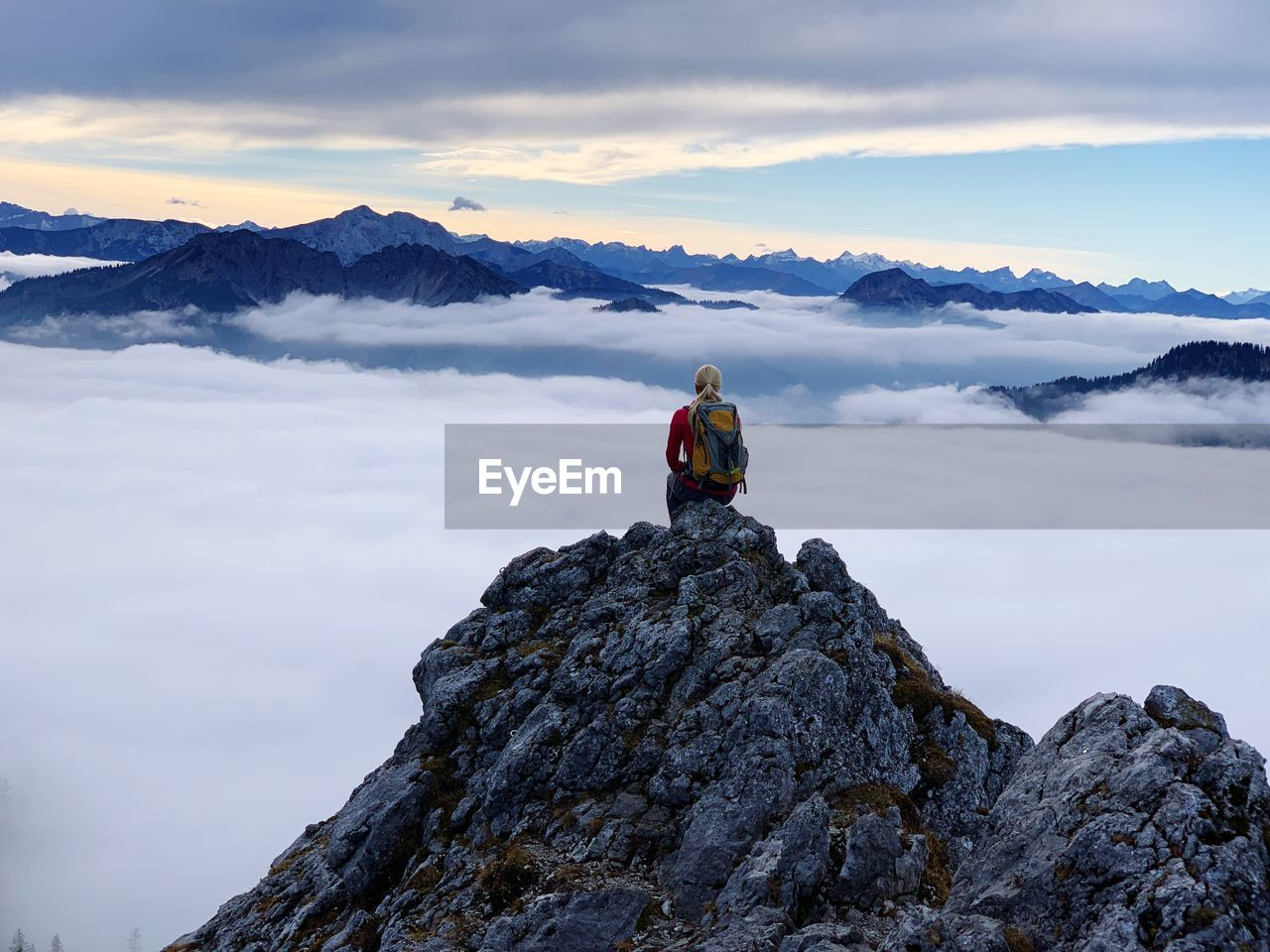 rock, mountain, rock - object, solid, sky, cloud - sky, scenics - nature, real people, leisure activity, one person, beauty in nature, lifestyles, tranquil scene, mountain range, nature, activity, tranquility, non-urban scene, sitting, vacations, mountain peak, snowcapped mountain, outdoors, formation