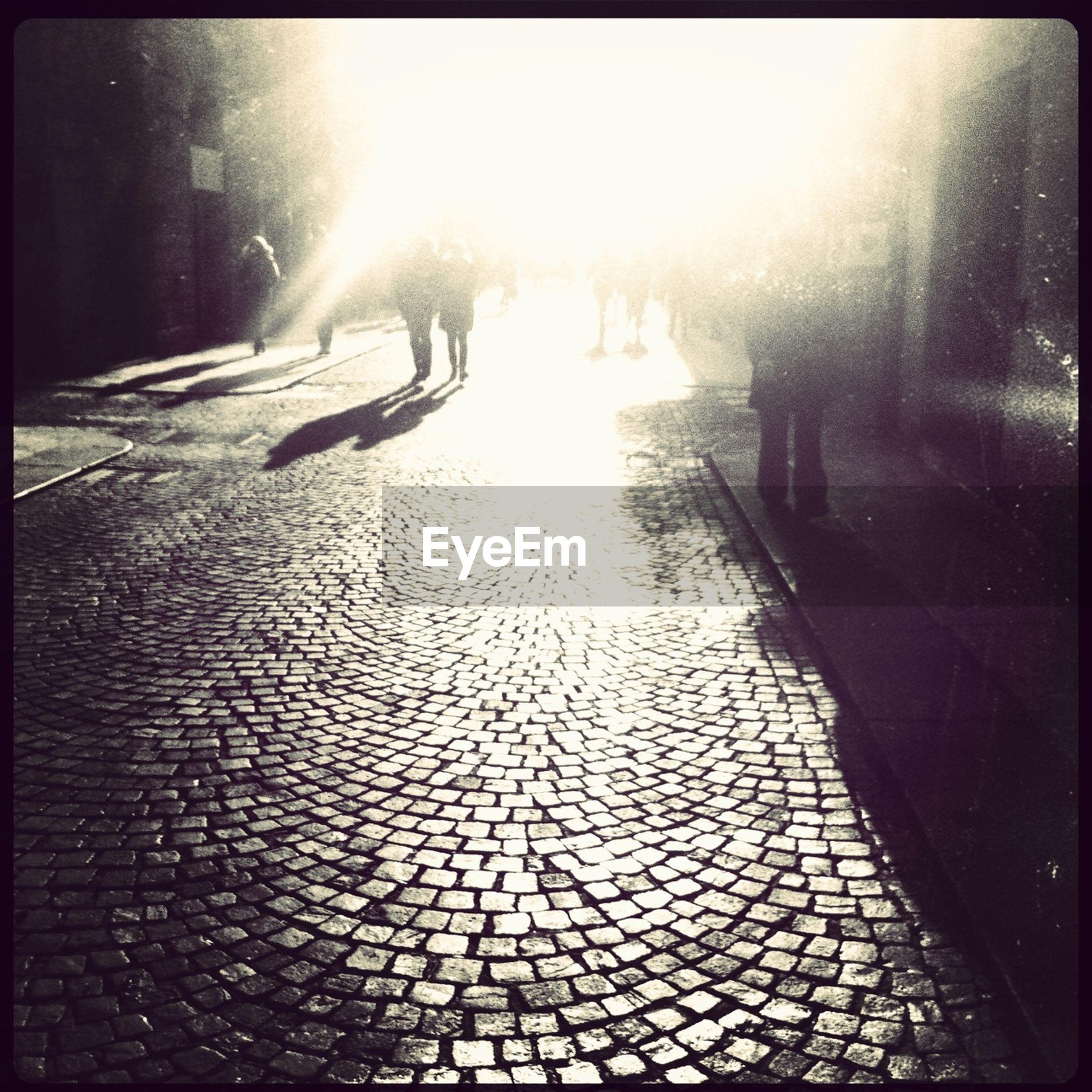 People walking in distance on cobblestone street