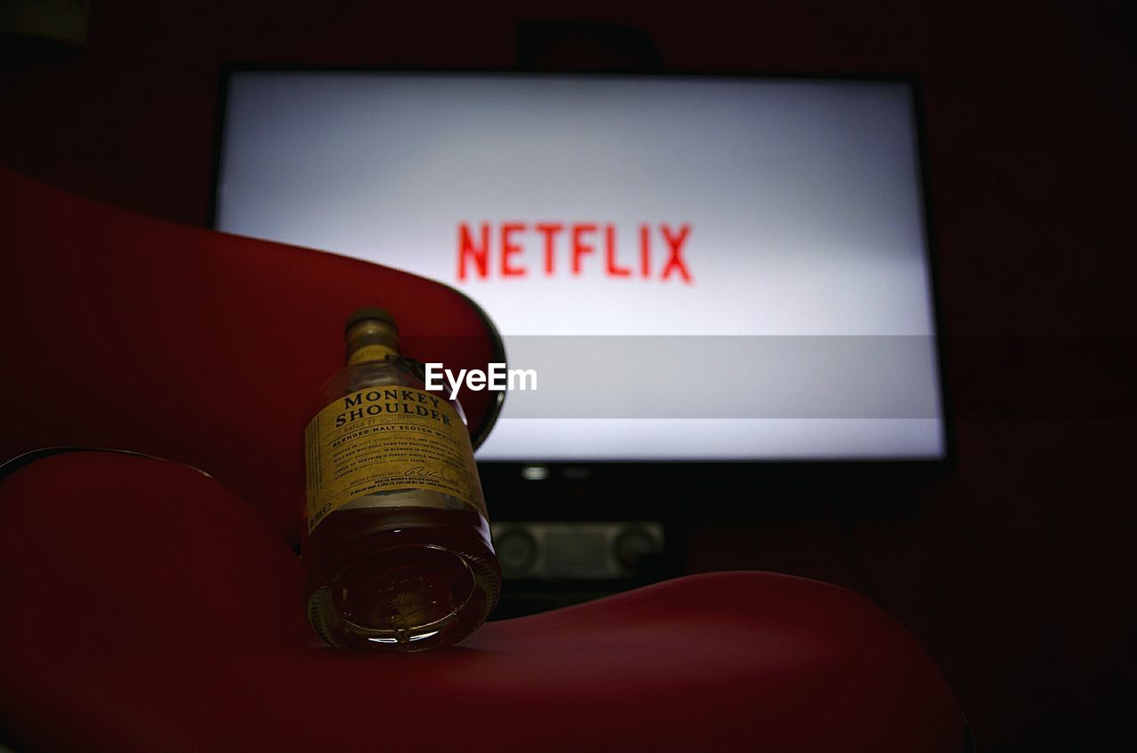 text, indoors, red, communication, home interior, close-up, alcohol, technology, no people, illuminated, day