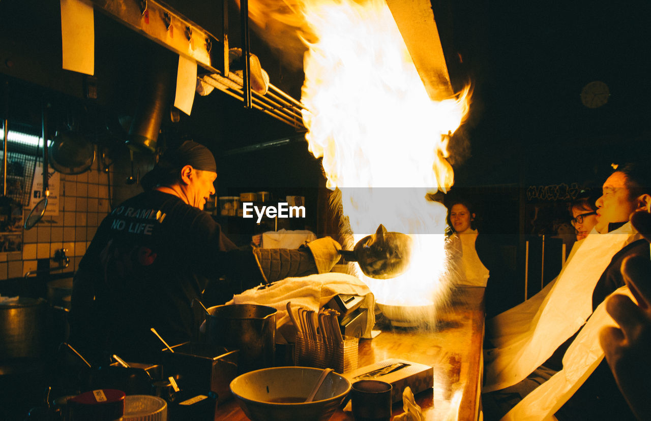real people, occupation, heat - temperature, working, men, flame, commercial kitchen, food and drink, preparation, food, chef, preparing food, burning, food and drink establishment, uniform, indoors, chef's hat, protective workwear, night, freshness, one person, adult, people