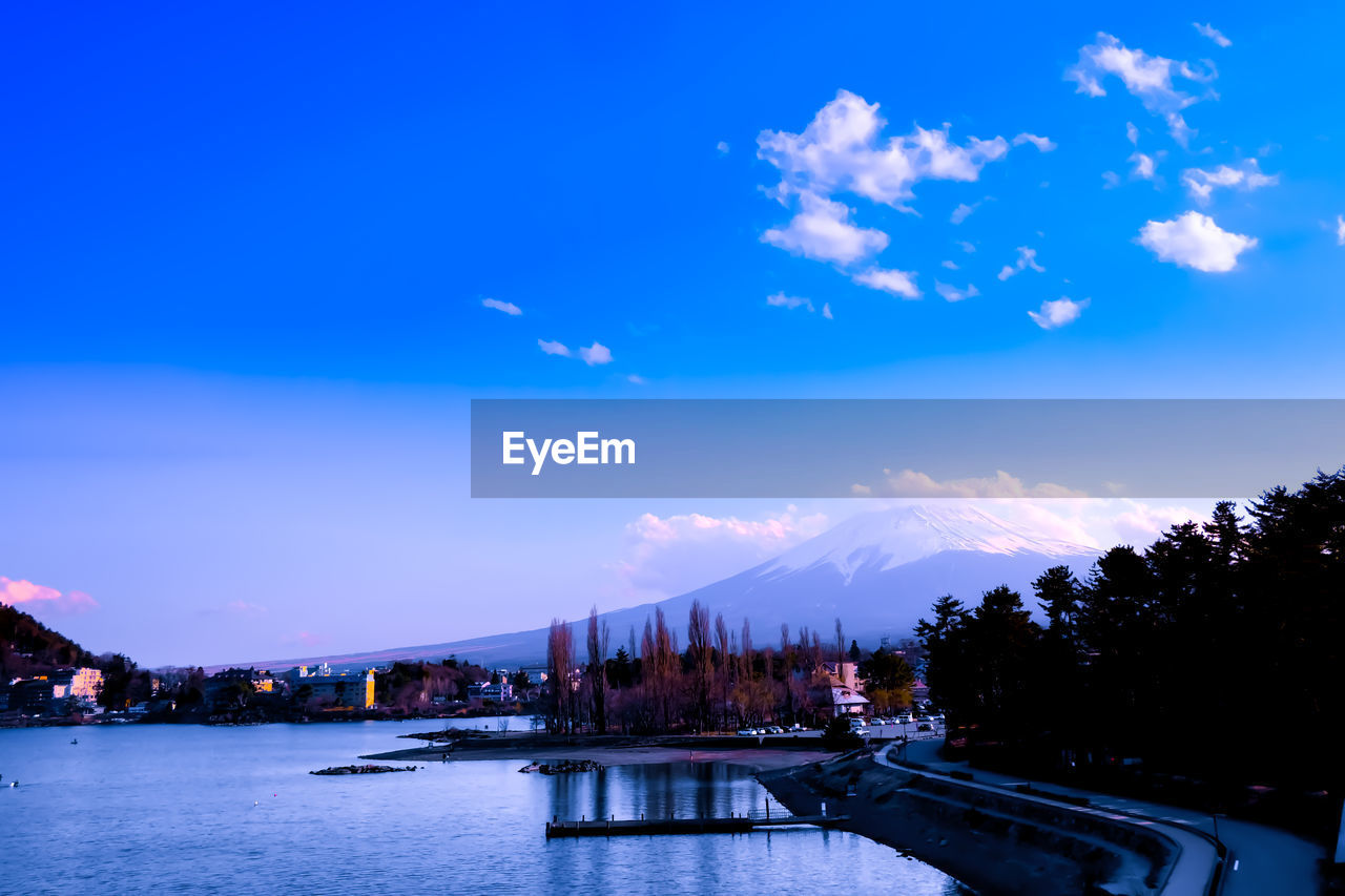 sky, water, cloud - sky, architecture, nature, tree, built structure, scenics - nature, blue, beauty in nature, building exterior, transportation, no people, waterfront, plant, mountain, river, city, tranquil scene, outdoors