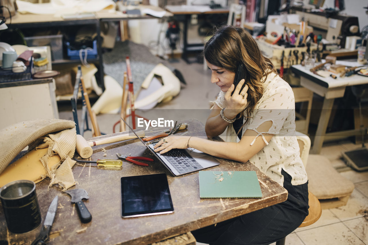 one person, real people, concentration, working, table, sitting, adult, holding, indoors, women, workshop, looking down, occupation, high angle view, art and craft, casual clothing, looking, skill, three quarter length, hairstyle, note pad