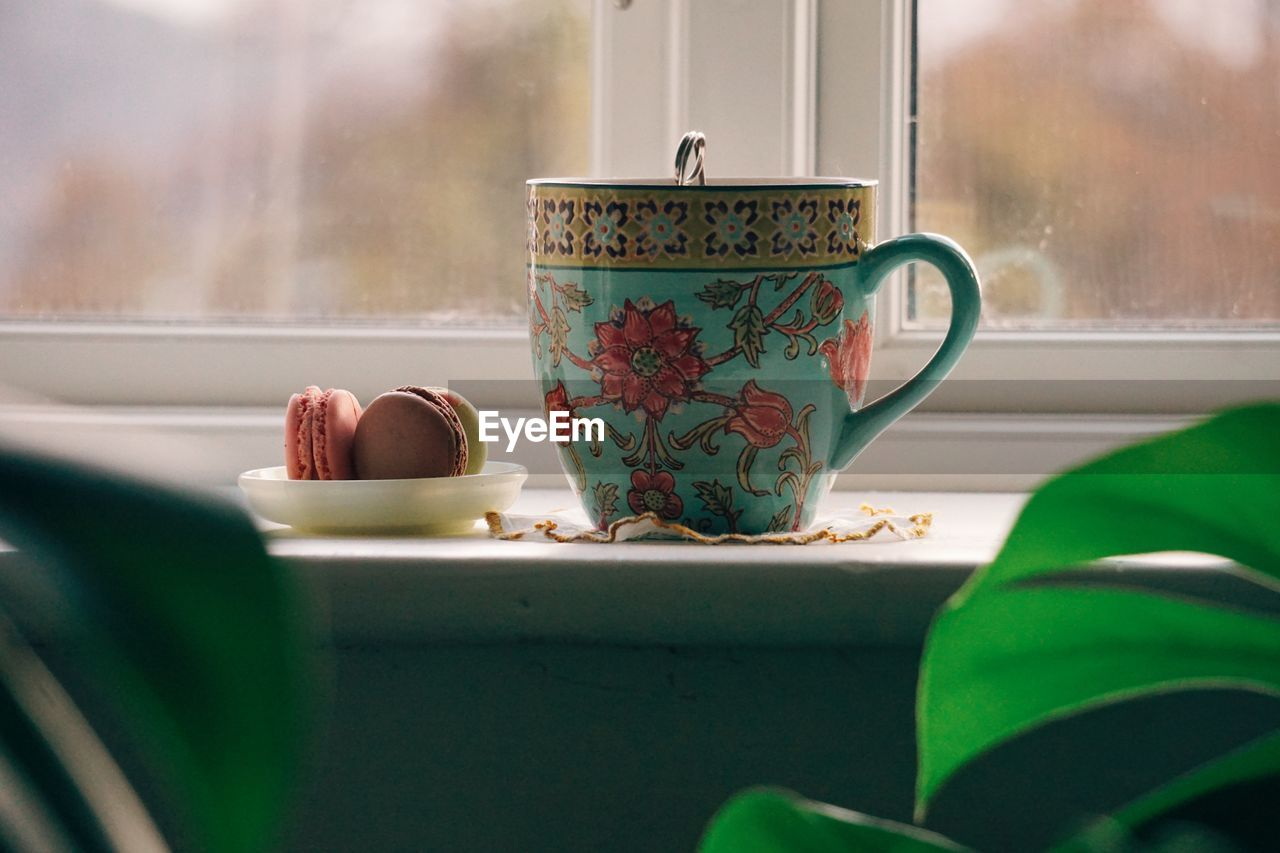 cup, floral pattern, mug, drink, indoors, window, table, transparent, food and drink, still life, refreshment, no people, pattern, crockery, tea, close-up, tea - hot drink, glass - material, tea cup, saucer, hot drink, teapot