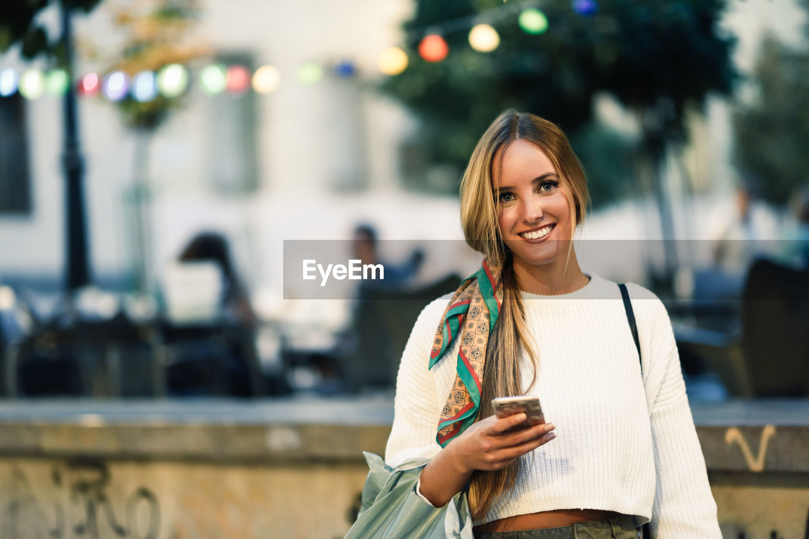 Portrait of smiling young woman using mobile phone while standing in city