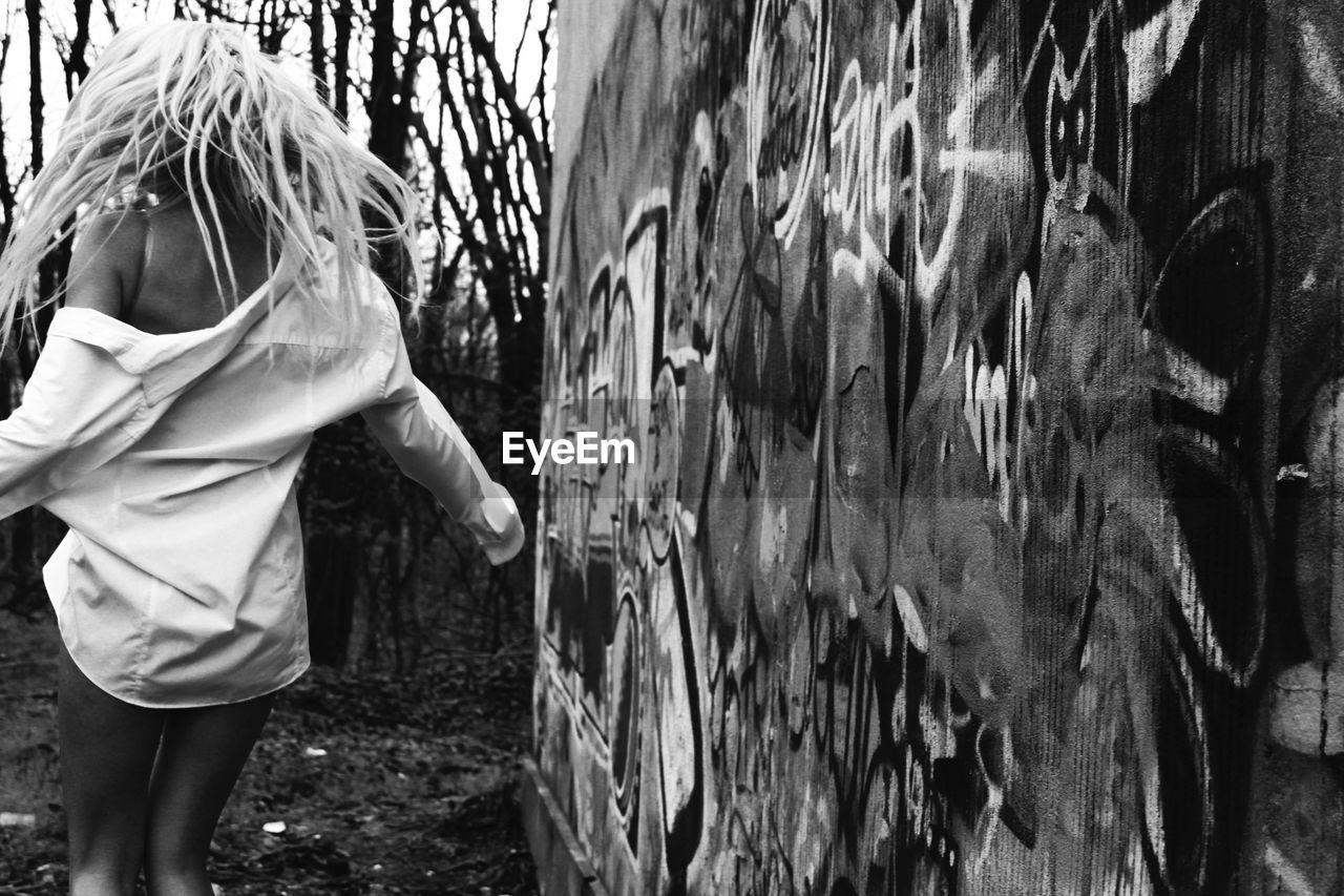 Rear view of woman with blond hair standing by graffiti wall