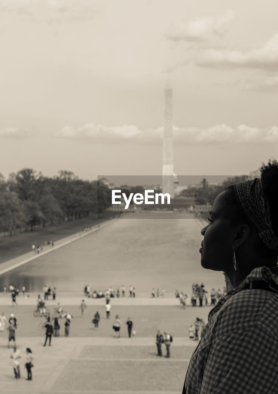Young woman standing in front of washington monument against sky