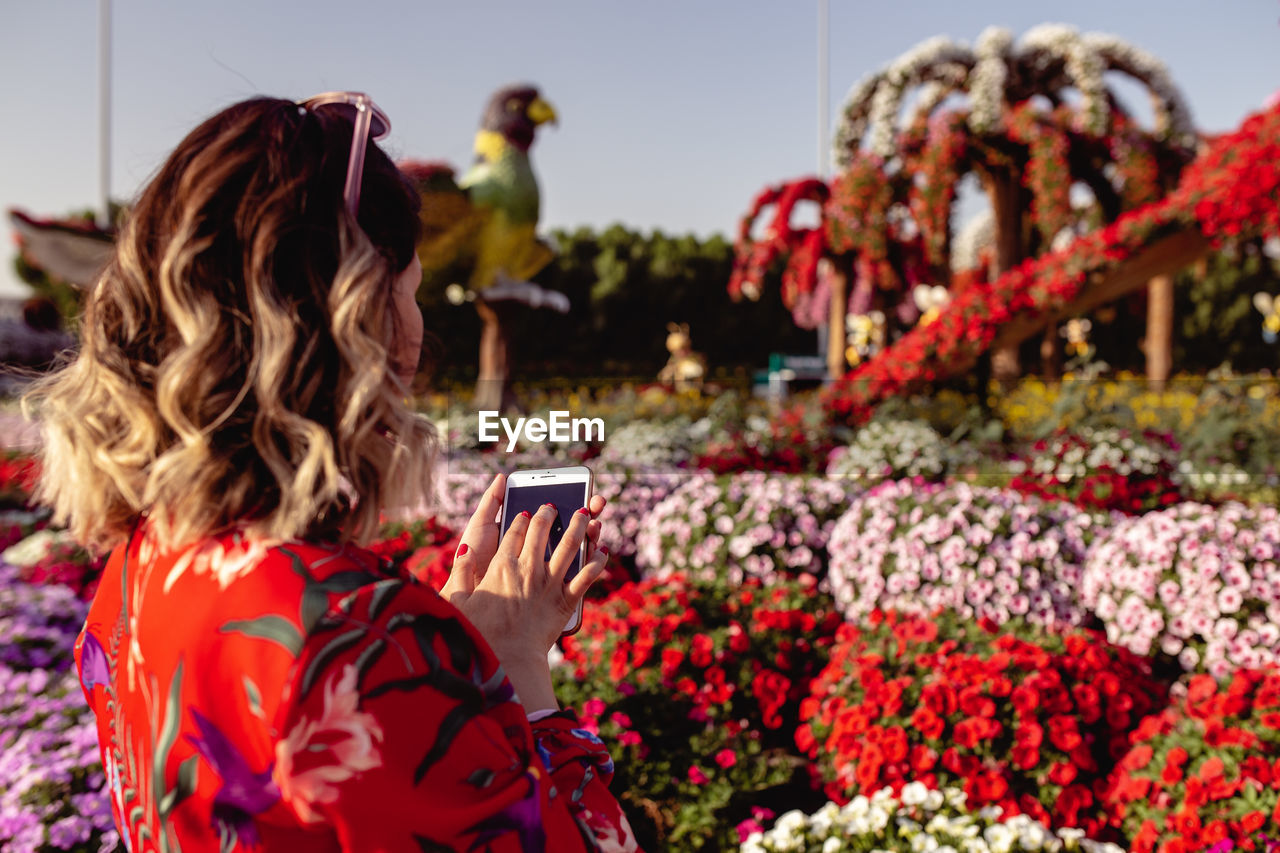 Close-Up Of Young Woman Using Mobile Phone While Standing In Ornamental Garden