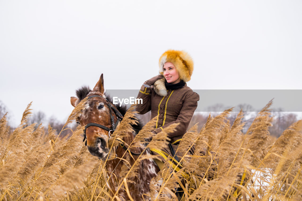 mammal, sky, field, animal themes, domestic animals, one person, animal, real people, domestic, land, clear sky, leisure activity, winter, pets, nature, lifestyles, one animal, day, warm clothing, outdoors