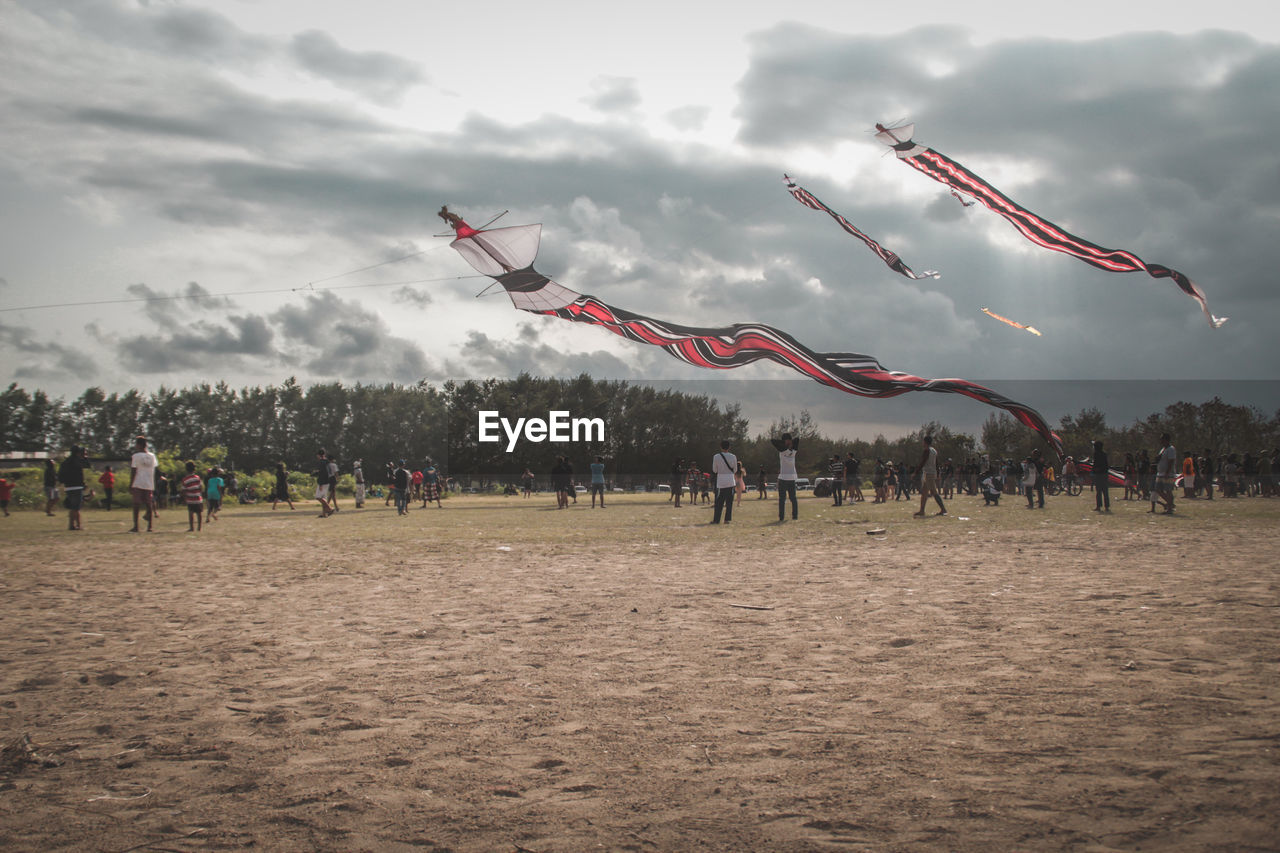 cloud - sky, real people, sky, group of people, crowd, flying, sport, nature, land, day, large group of people, leisure activity, team sport, kite - toy, outdoors, kite, men, playing, lifestyles, wind