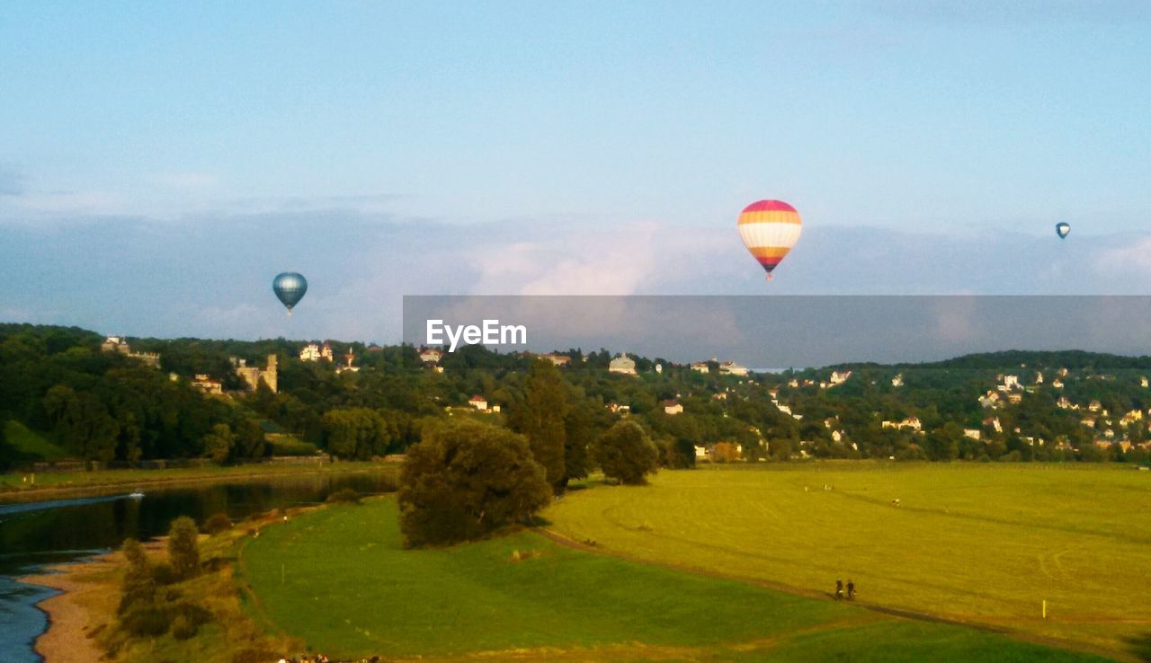 hot air balloon, flying, mid-air, transportation, adventure, nature, landscape, grass, sky, field, ballooning festival, scenics, tree, tranquil scene, journey, outdoors, beauty in nature, leisure activity, air vehicle, sport, no people, vacations, day, parachute