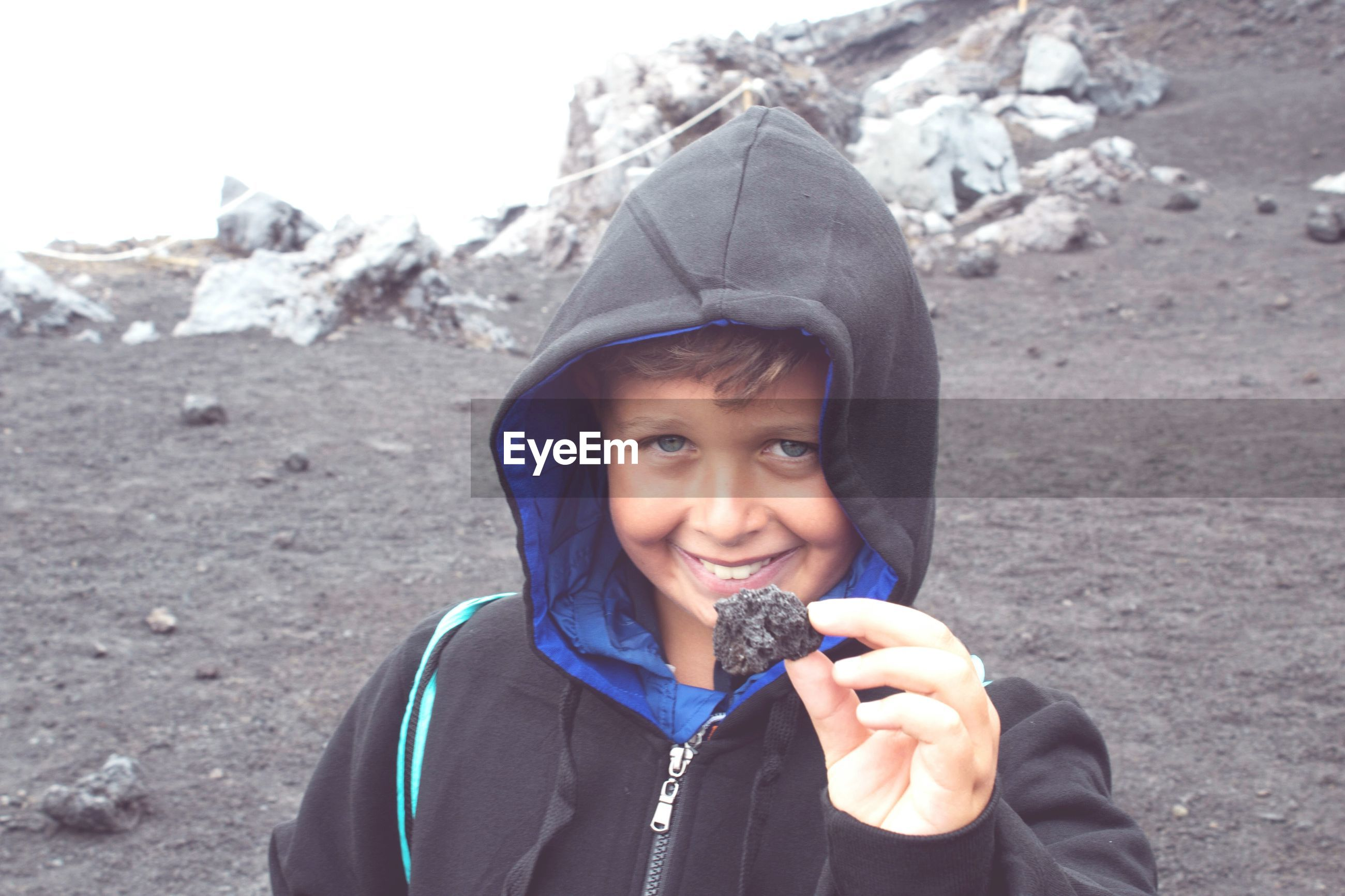 Portrait of smiling boy holding rock