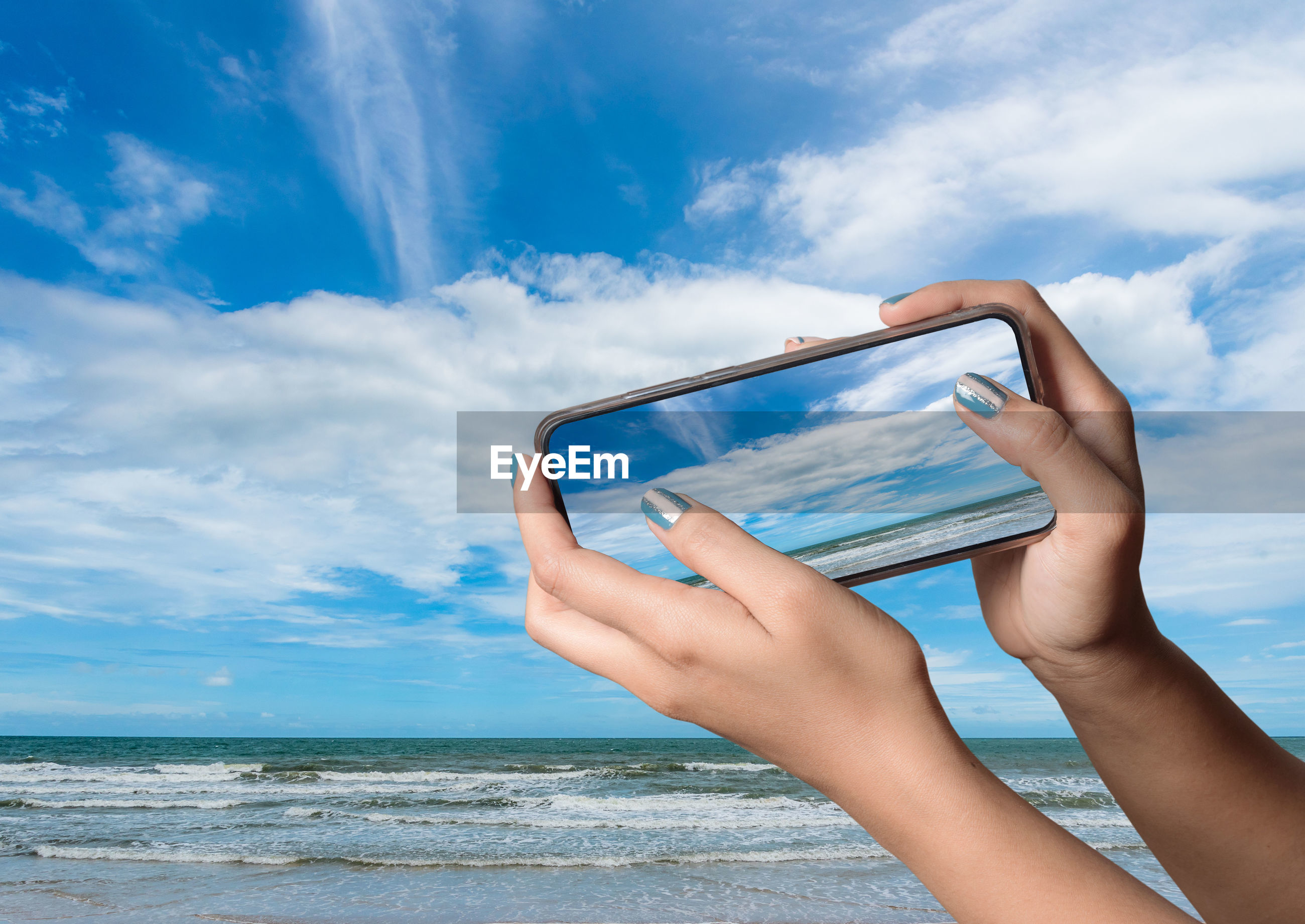 Cropped hand of woman using mobile phone against sea