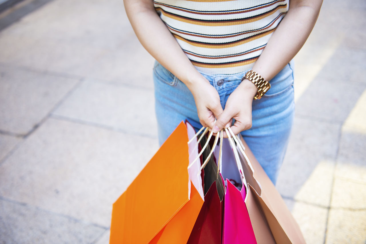 Midsection of woman holding shopping bags standing on footpath in city