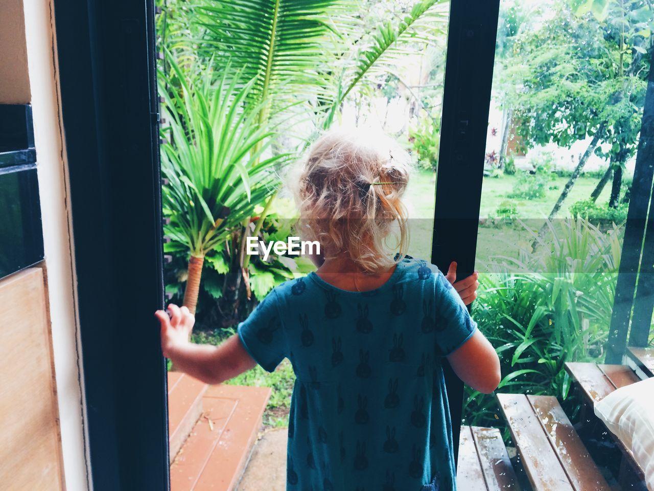 Rear View Of Child Opening Door