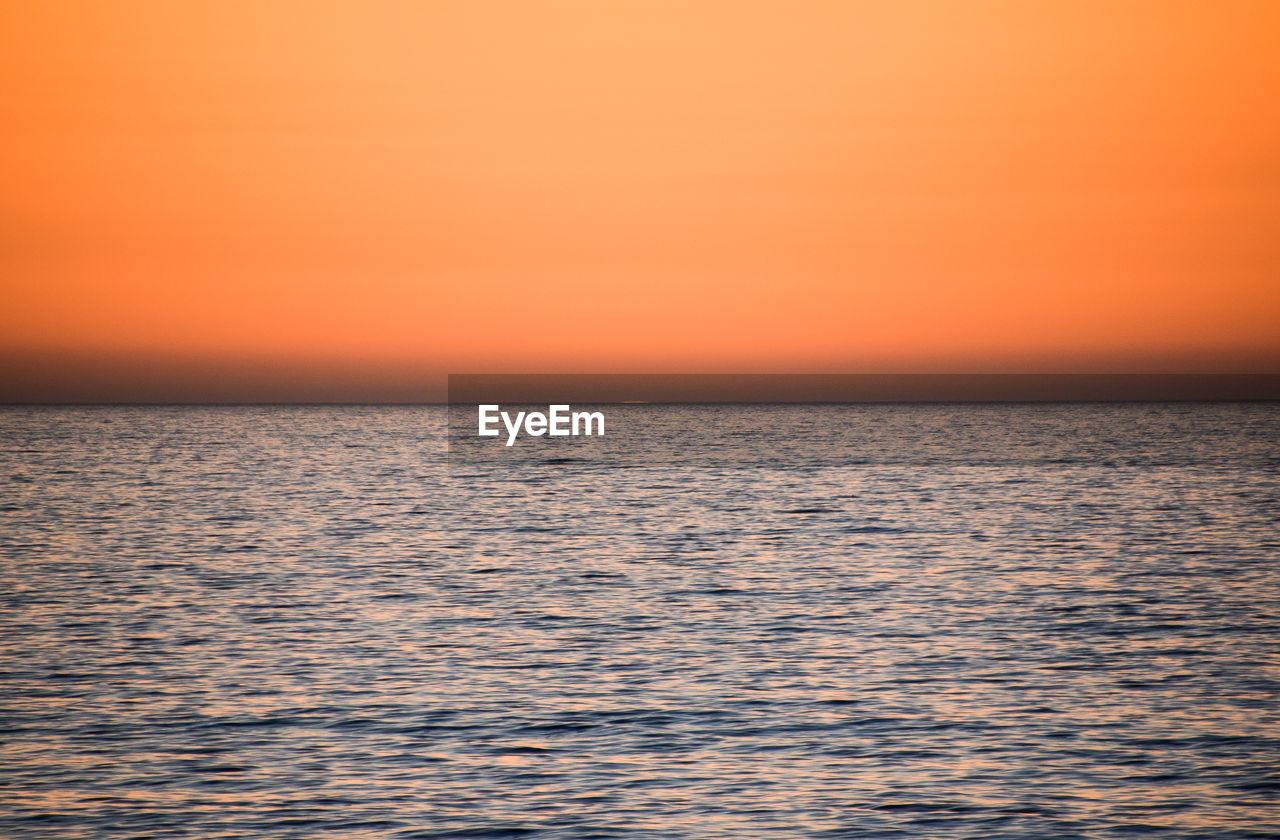 sunset, tranquil scene, beauty in nature, scenics, sea, tranquility, nature, idyllic, water, orange color, rippled, horizon over water, no people, sky, outdoors, waterfront, silhouette, clear sky, day