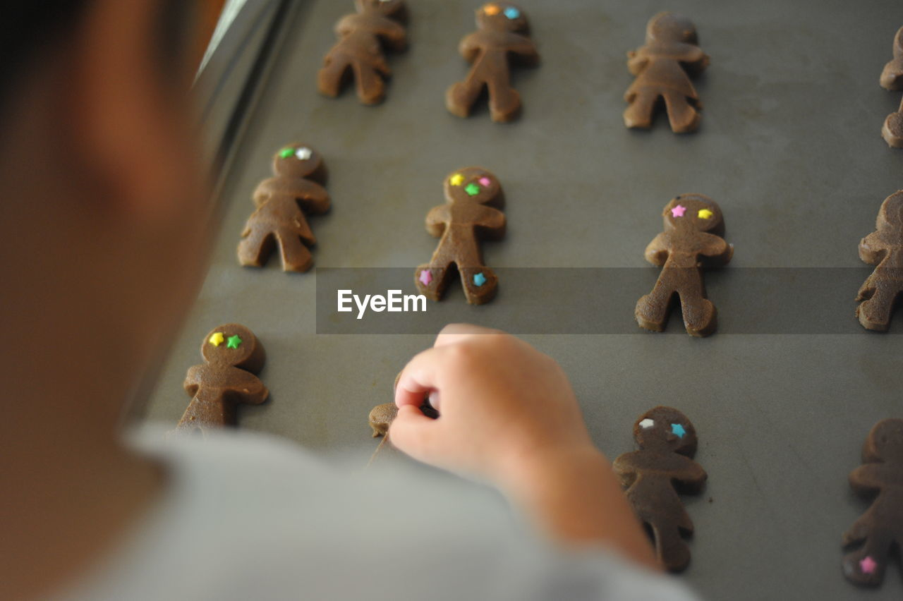 Cropped Image Of Boy Arranging Gingerbread Cookies On Tray