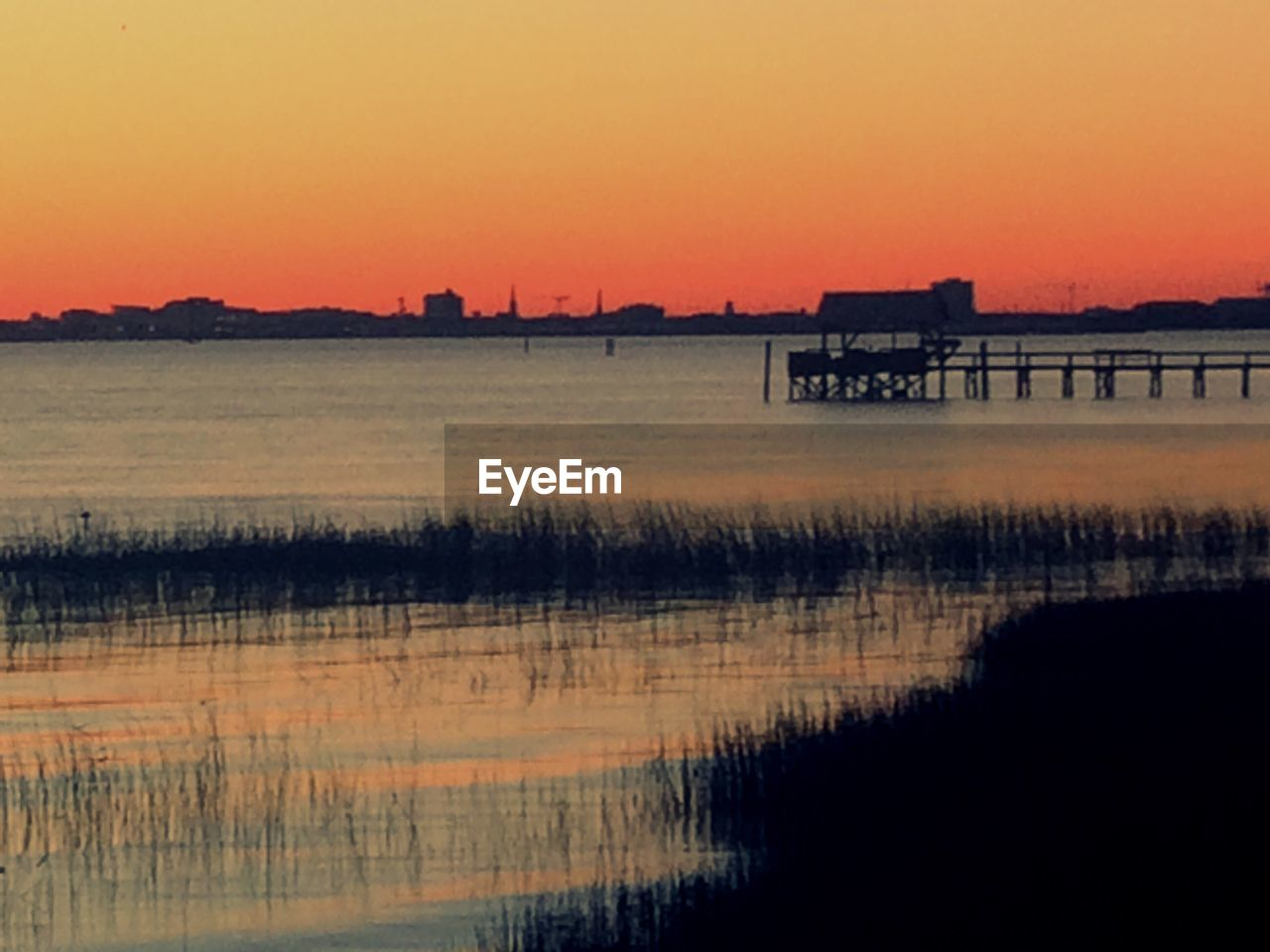 sunset, silhouette, reflection, water, beauty in nature, nature, scenics, orange color, sky, built structure, tranquil scene, tranquility, lake, waterfront, outdoors, architecture, no people, building exterior, day