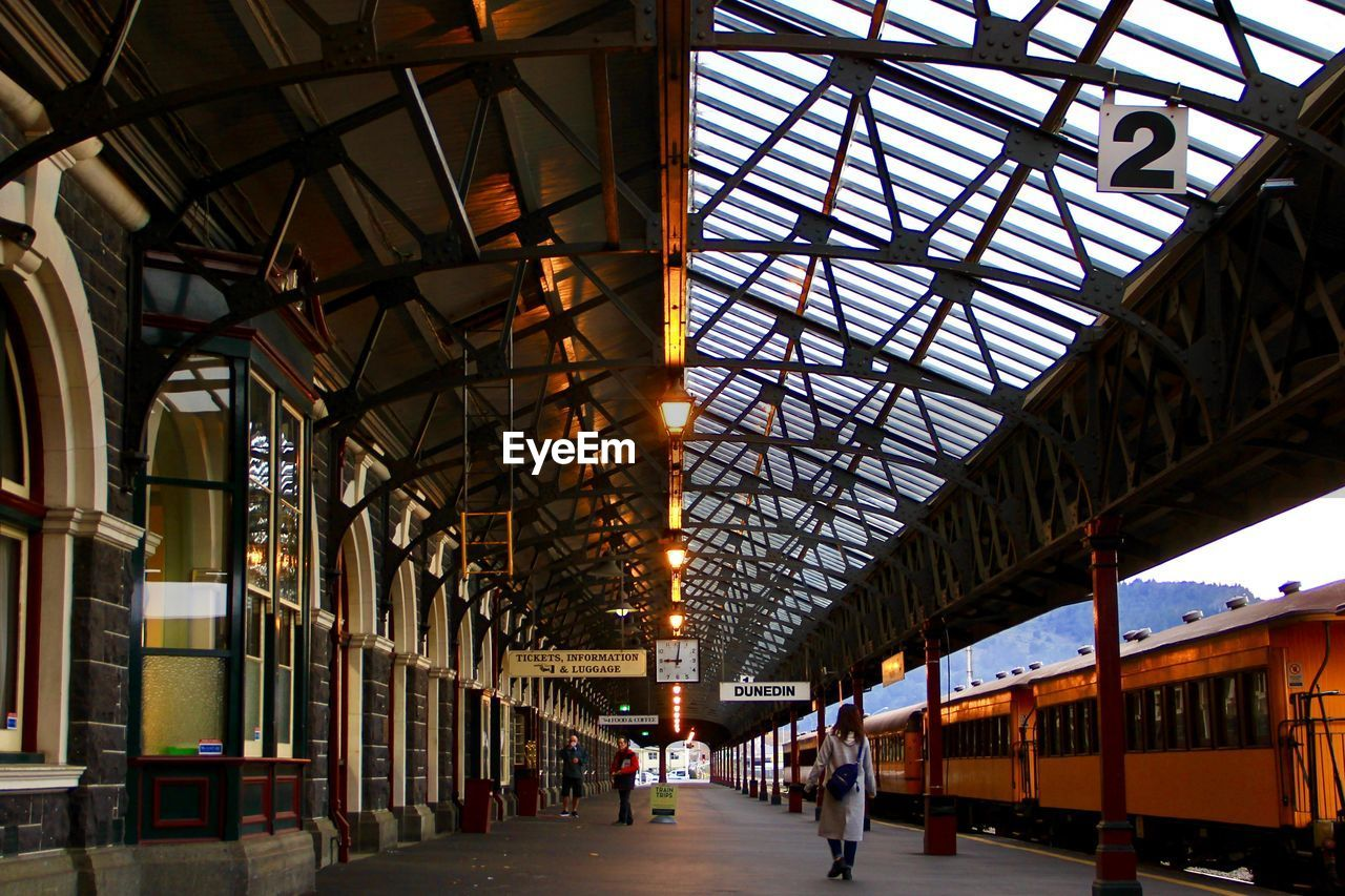 architecture, ceiling, built structure, indoors, transportation, railroad station, railroad station platform, rail transportation, mode of transportation, day, roof, lighting equipment, public transportation, train, incidental people, metal, illuminated, sunlight, men, station