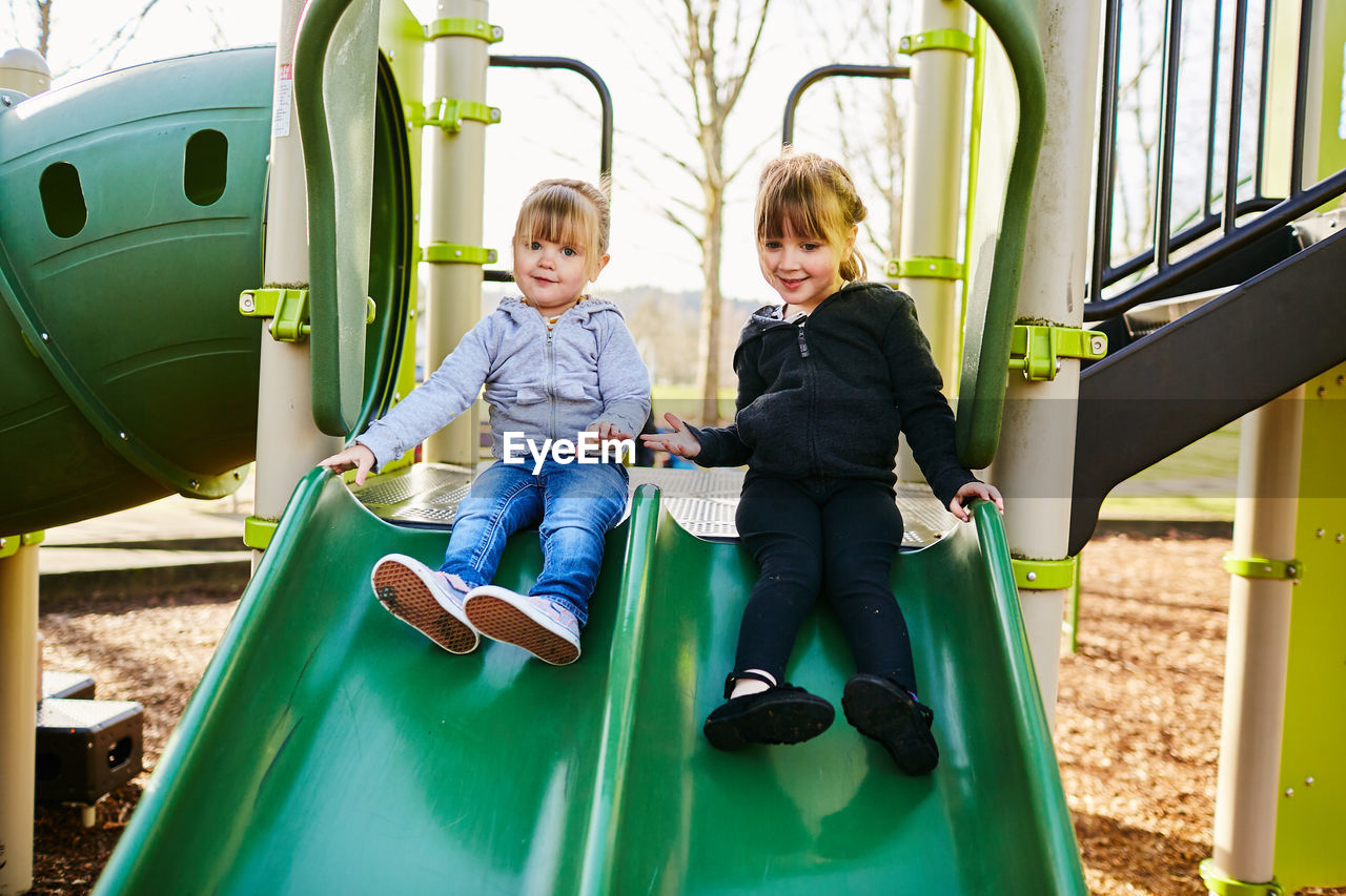 child, childhood, real people, two people, casual clothing, women, females, full length, boys, girls, leisure activity, front view, sitting, innocence, cute, sibling, family, day, outdoor play equipment, sister, outdoors