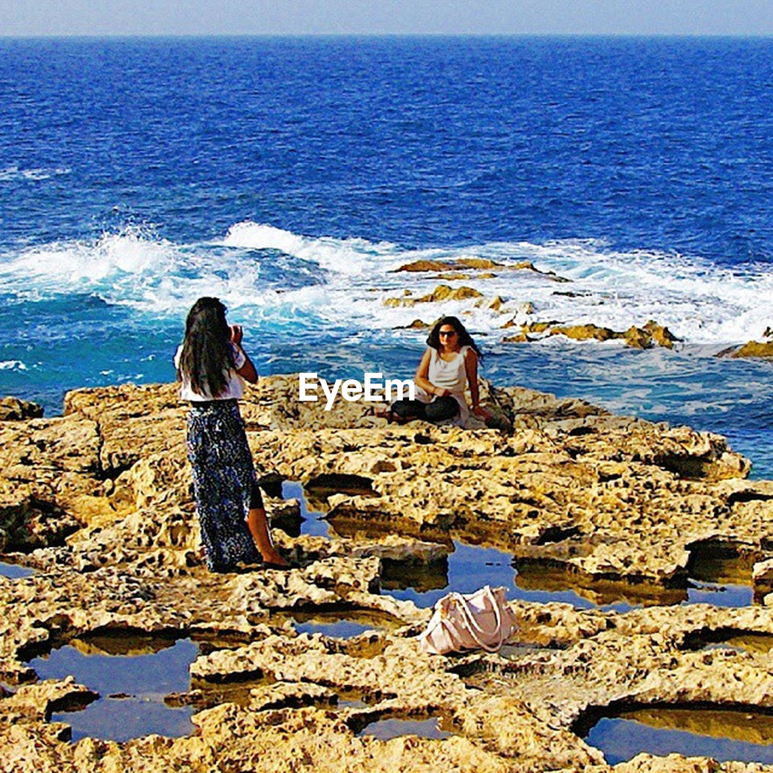 sea, water, lifestyles, rock - object, horizon over water, leisure activity, sitting, beach, scenics, tranquility, beauty in nature, vacations, rock formation, nature, men, tranquil scene, shore, rear view