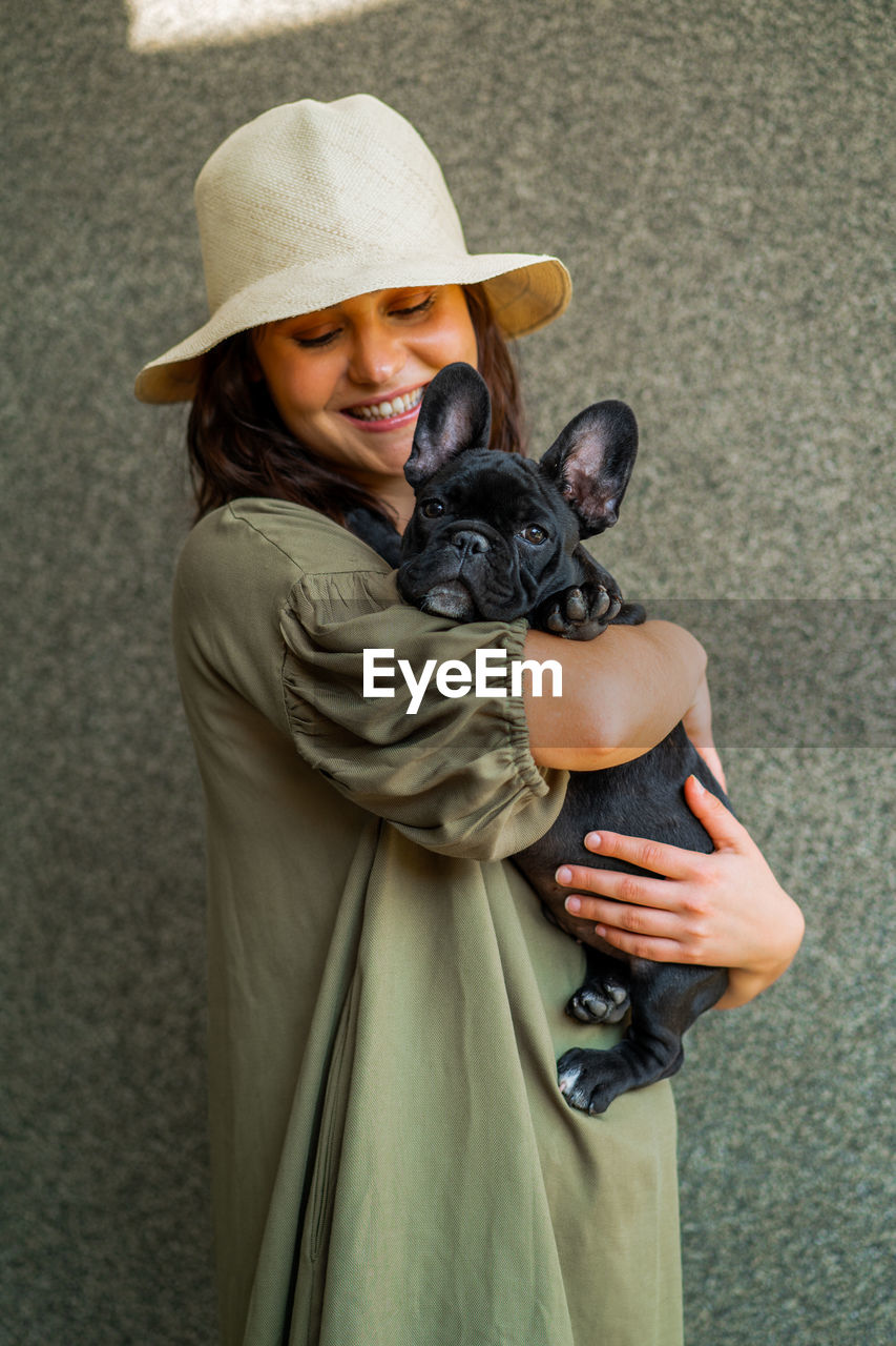MIDSECTION OF WOMAN HOLDING DOG WITH HAT