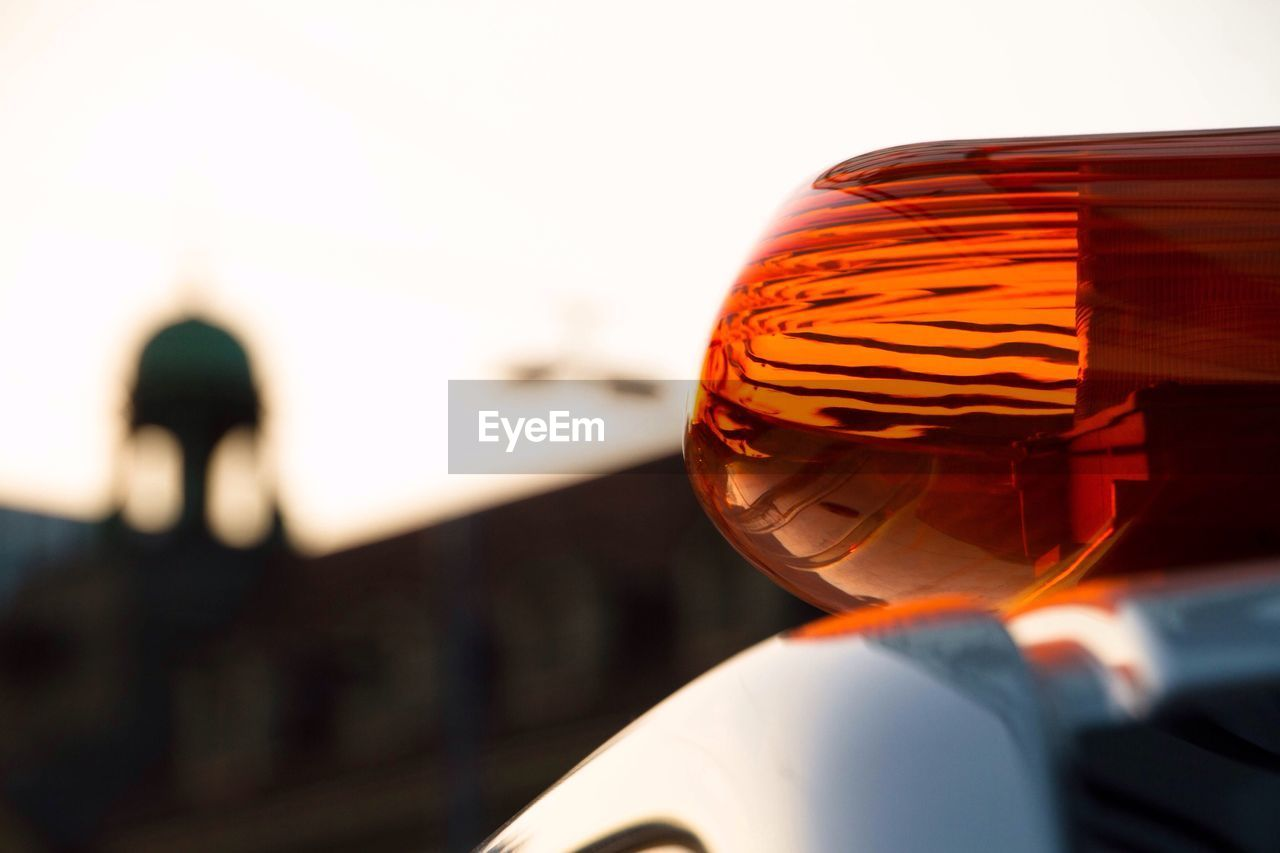 Close-Up Of Red Emergency Light On Car Against Sky During Sunset