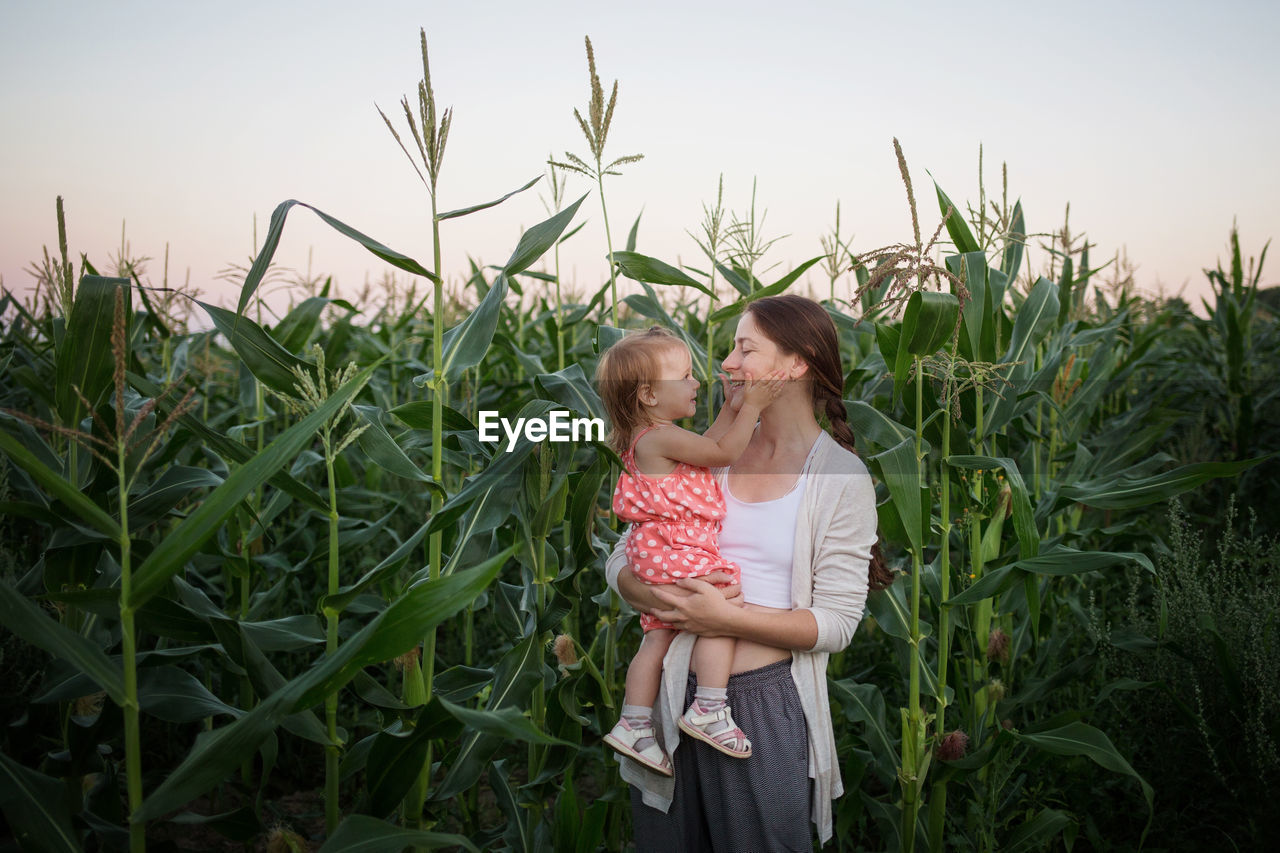 MOTHER AND DAUGHTER ON FIELD AGAINST PLANTS ON FARM