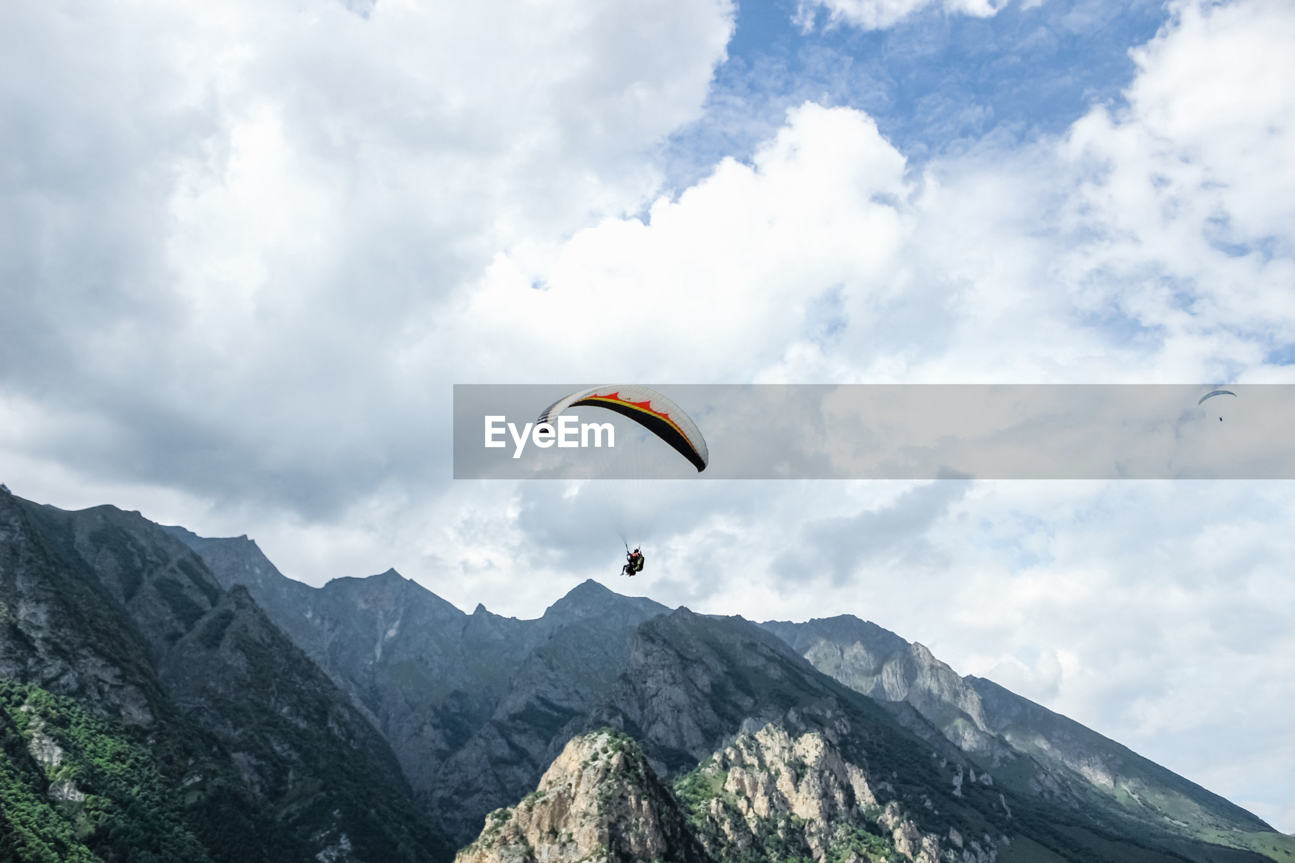 LOW ANGLE VIEW OF PARAGLIDING AGAINST MOUNTAIN