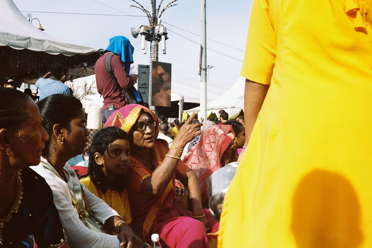 group of people, crowd, real people, men, large group of people, lifestyles, women, day, adult, togetherness, celebration, leisure activity, traditional clothing, yellow, casual clothing, event, standing, belief, outdoors