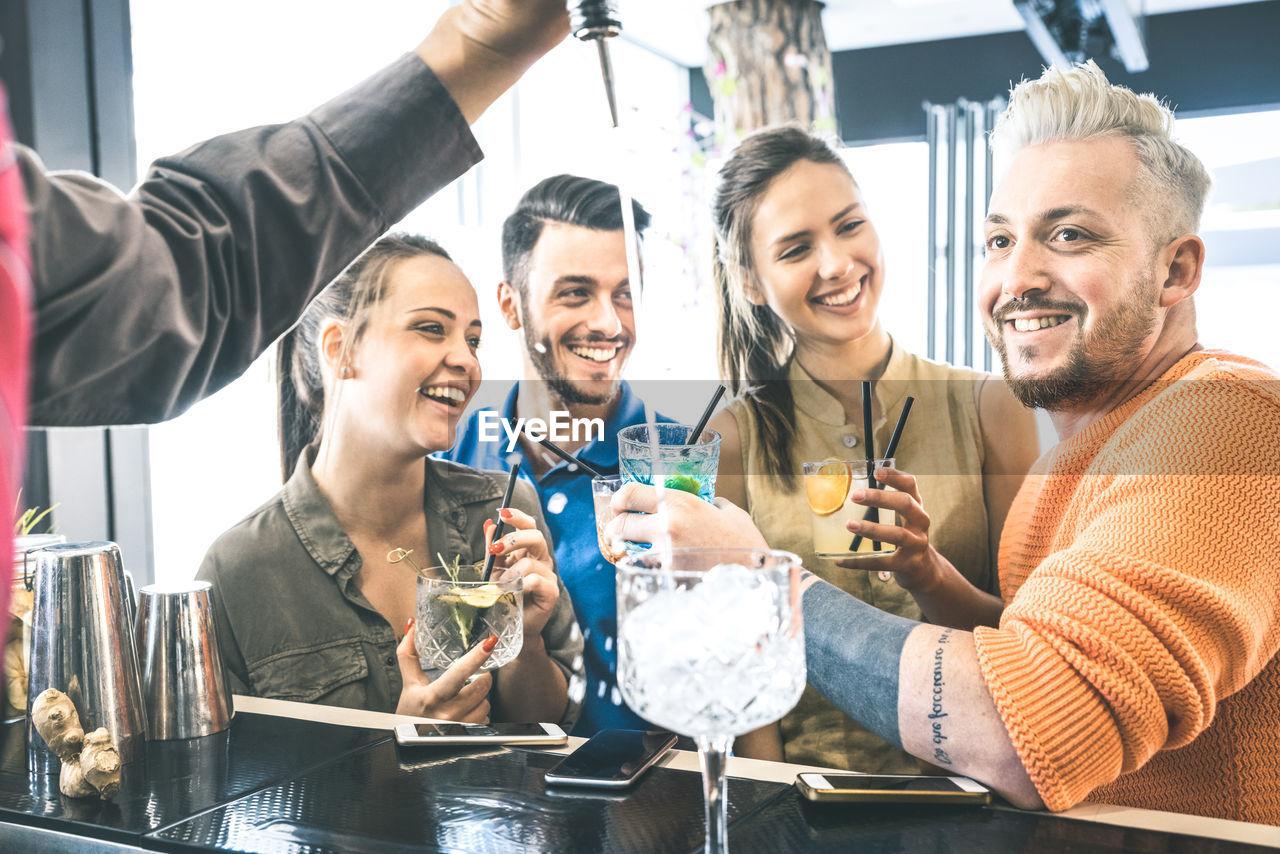 Happy friends enjoying drinks in bar