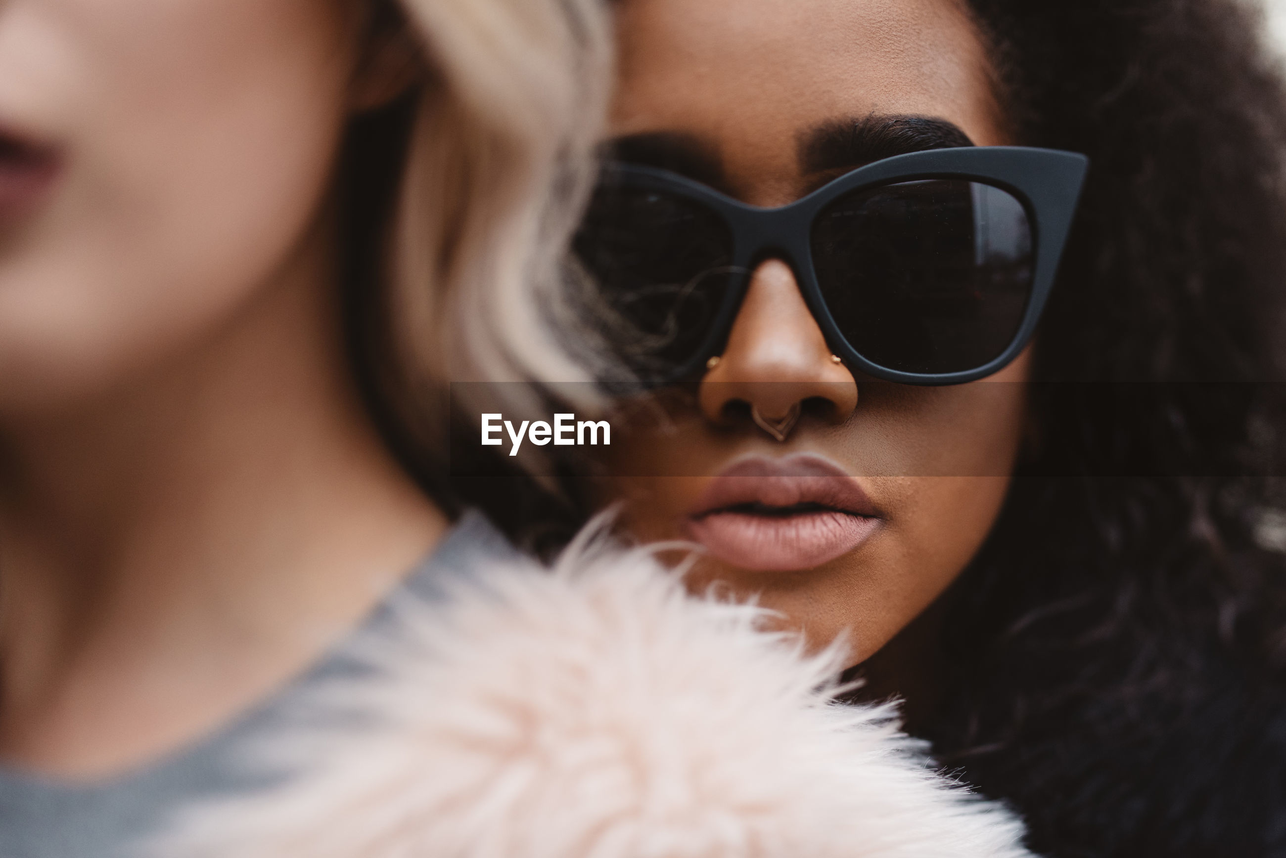Portrait of woman wearing black sunglasses while standing behind friend