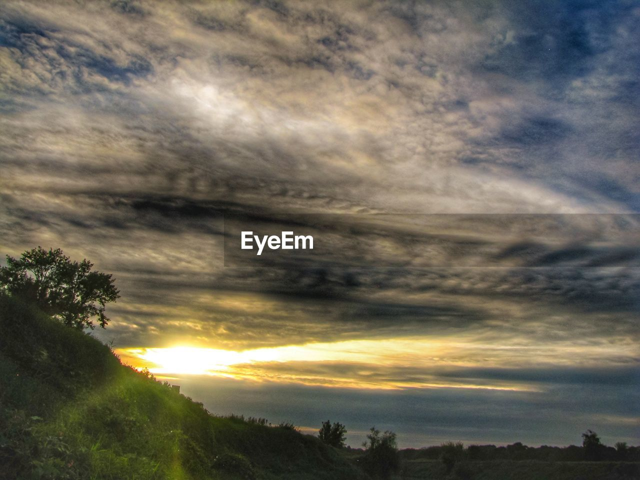 cloud - sky, sky, sunset, beauty in nature, scenics - nature, tranquility, tranquil scene, nature, tree, plant, orange color, idyllic, sun, no people, environment, sunbeam, sunlight, dramatic sky, landscape, outdoors