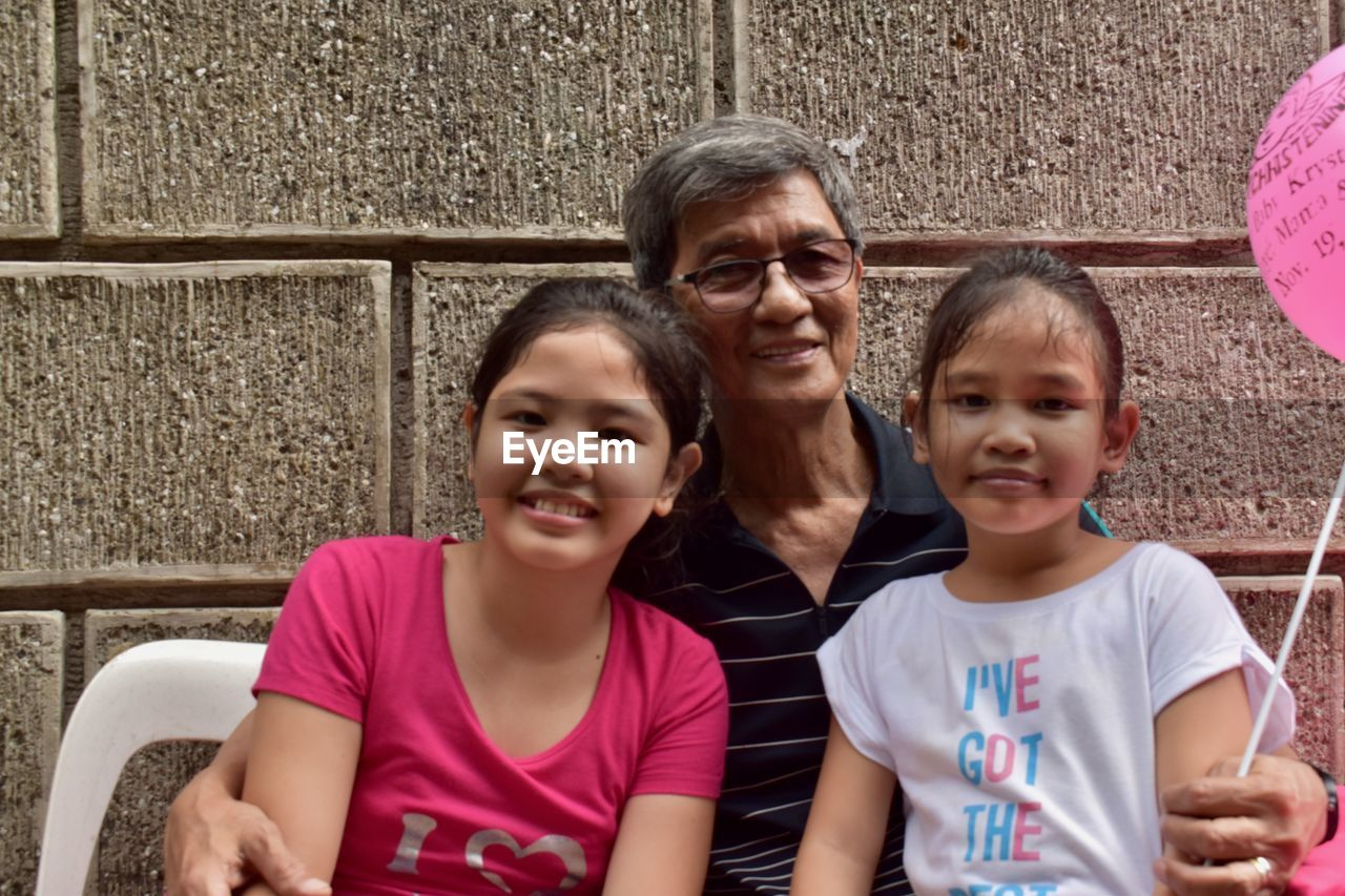 Portrait of smiling girls sitting with grandfather against wall