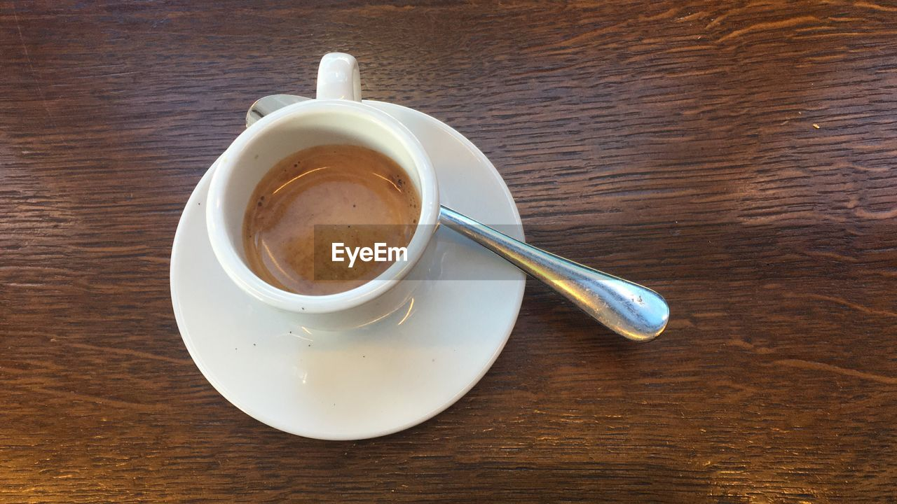 refreshment, coffee, drink, cup, coffee cup, coffee - drink, mug, food and drink, table, spoon, eating utensil, still life, kitchen utensil, crockery, saucer, indoors, high angle view, wood - material, freshness, no people, frothy drink, non-alcoholic beverage, teaspoon, wood grain