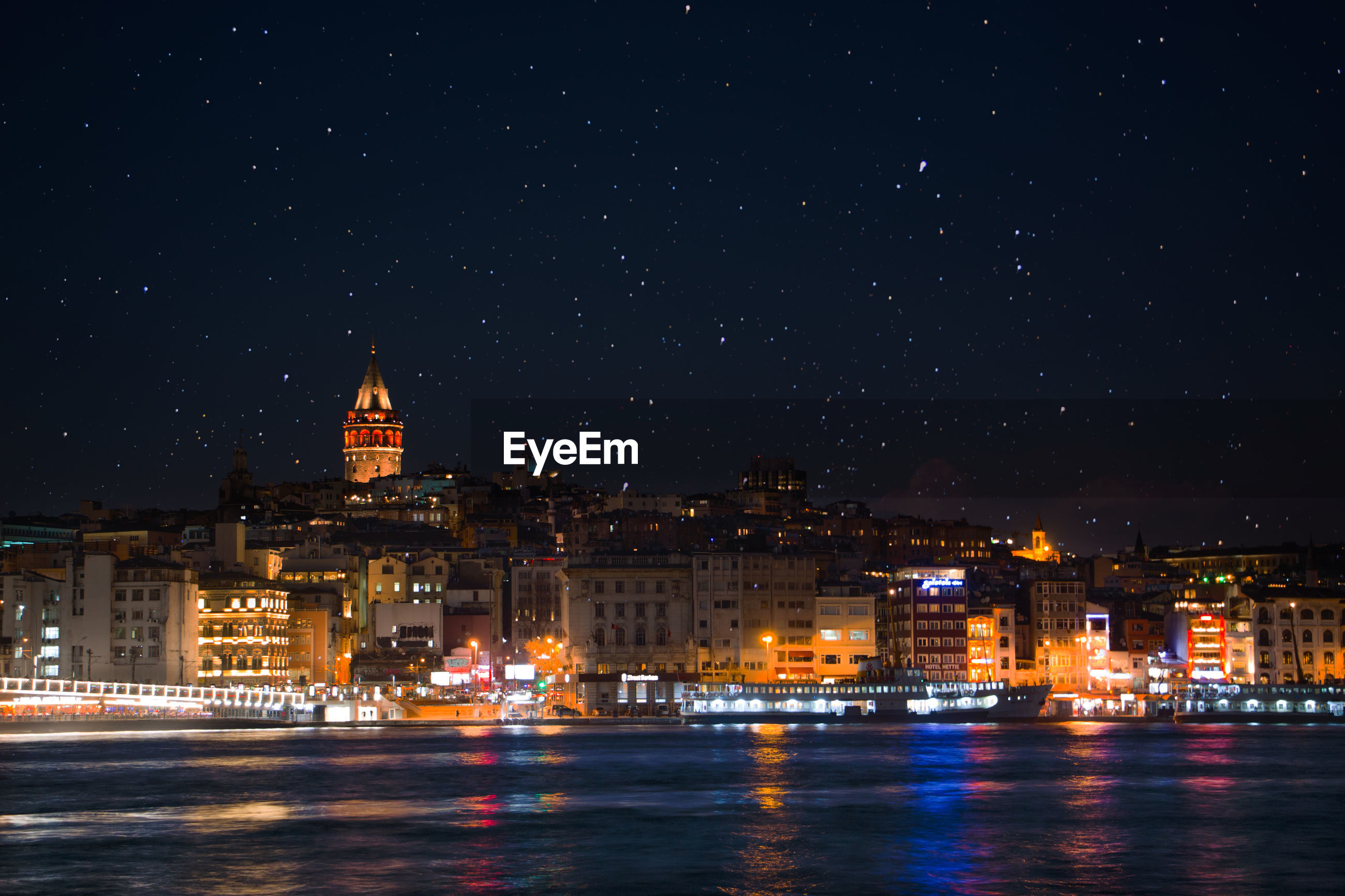 Illuminated city by river against star field at night