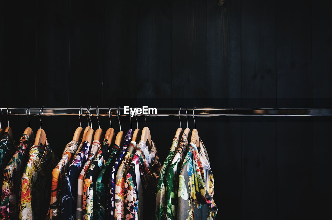 Clothes Hanging From Coathangers On Rack Against Wall In Shop