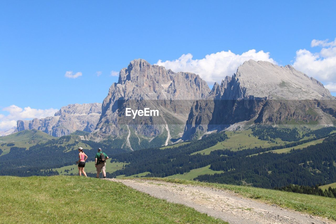 Rear view of people hiking by dolomites mountains