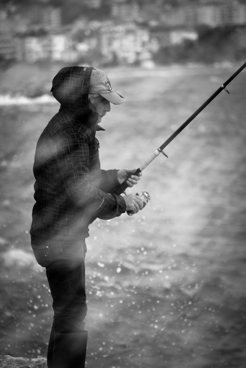 fishing, holding, outdoors, water, real people, one person, standing, day, men, fishing pole, nature, fishing tackle, close-up, sky, human hand, people