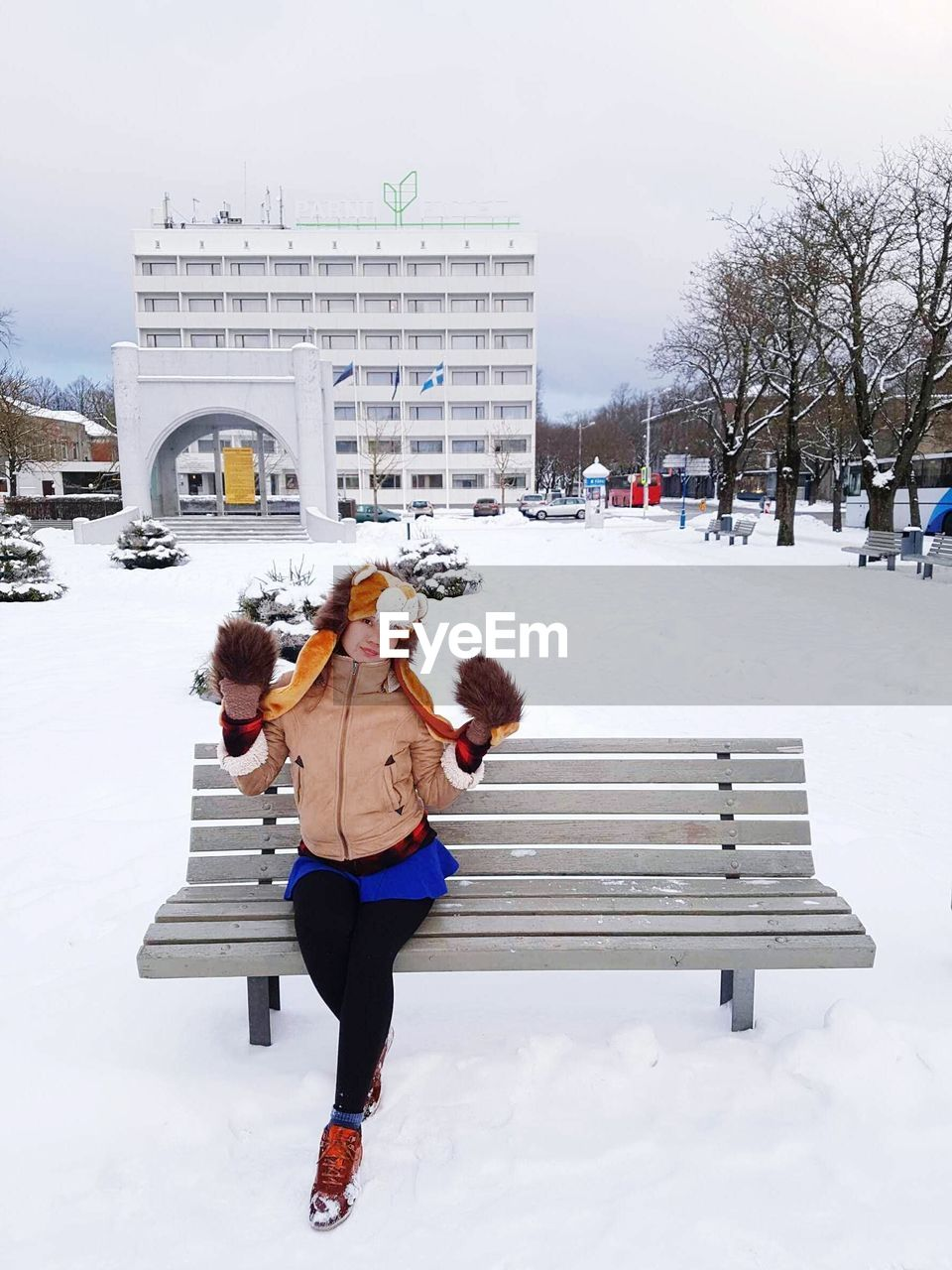 Full length portrait of woman sitting on bench during winter in city