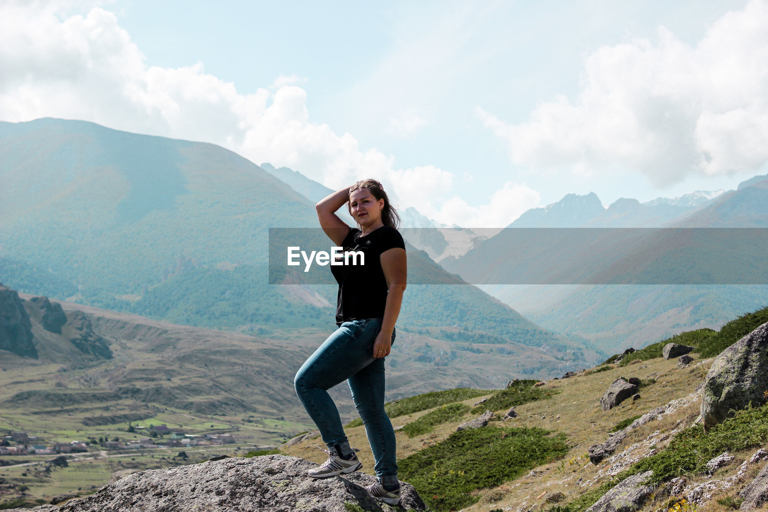 Portrait of woman standing on rock against mountain range
