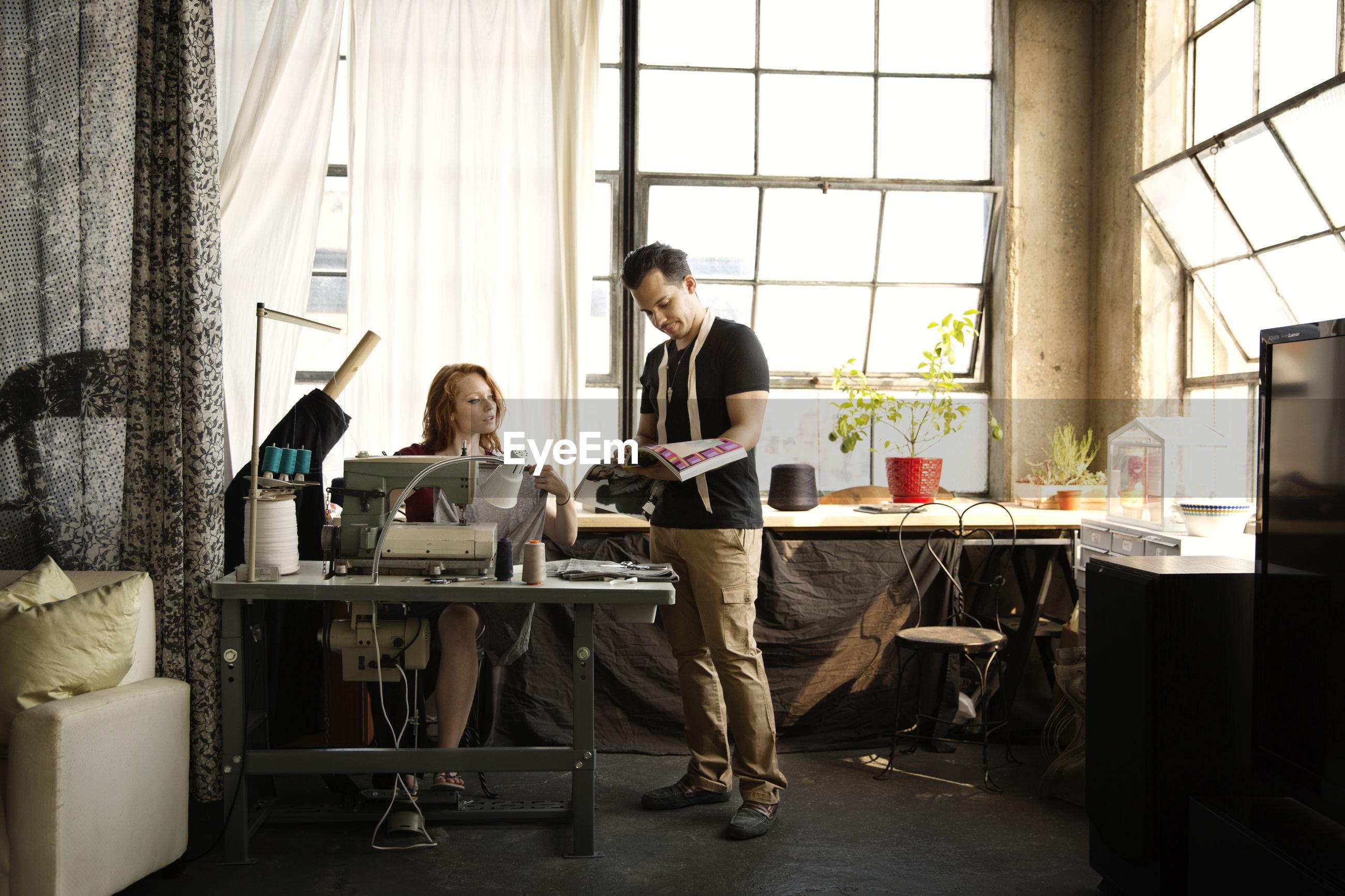 Fashion designers working against windows at workshop