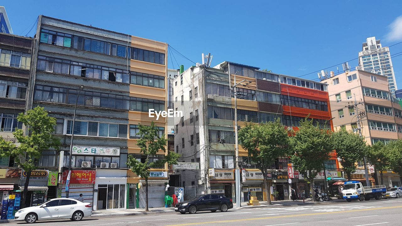 building exterior, architecture, built structure, mode of transportation, motor vehicle, car, transportation, city, building, sky, land vehicle, plant, tree, clear sky, residential district, nature, day, street, road, window, outdoors, apartment