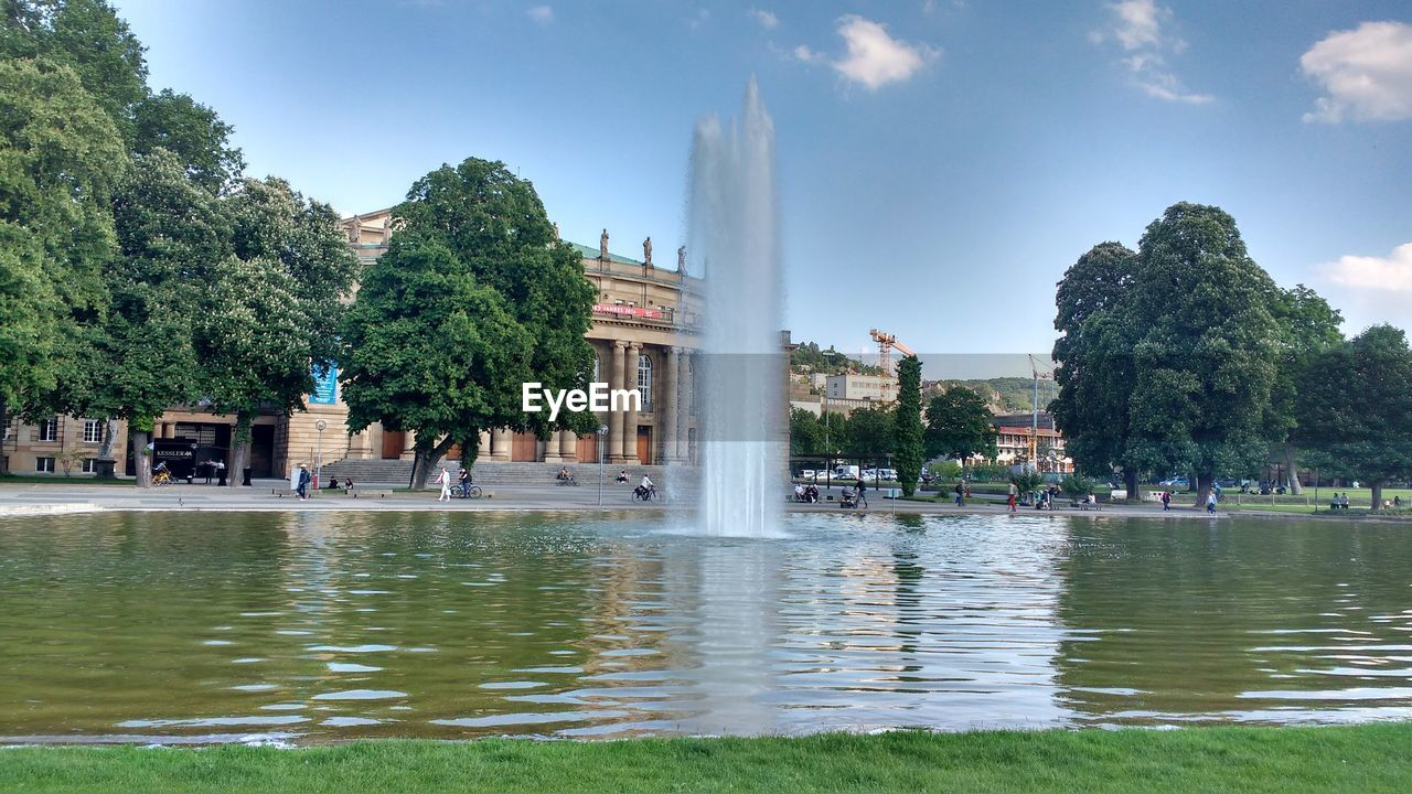 water, architecture, built structure, fountain, tree, building exterior, travel, tourism, travel destinations, day, sky, outdoors, waterfront, vacations, large group of people, reflecting pool, real people, spraying, nature, people