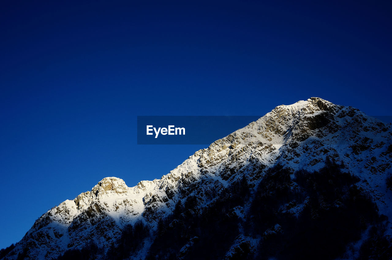 cold temperature, snow, winter, blue, nature, copy space, low angle view, mountain, beauty in nature, clear sky, tranquility, tranquil scene, weather, scenics, day, snowcapped mountain, outdoors, no people, frozen, mountain peak, mountain range