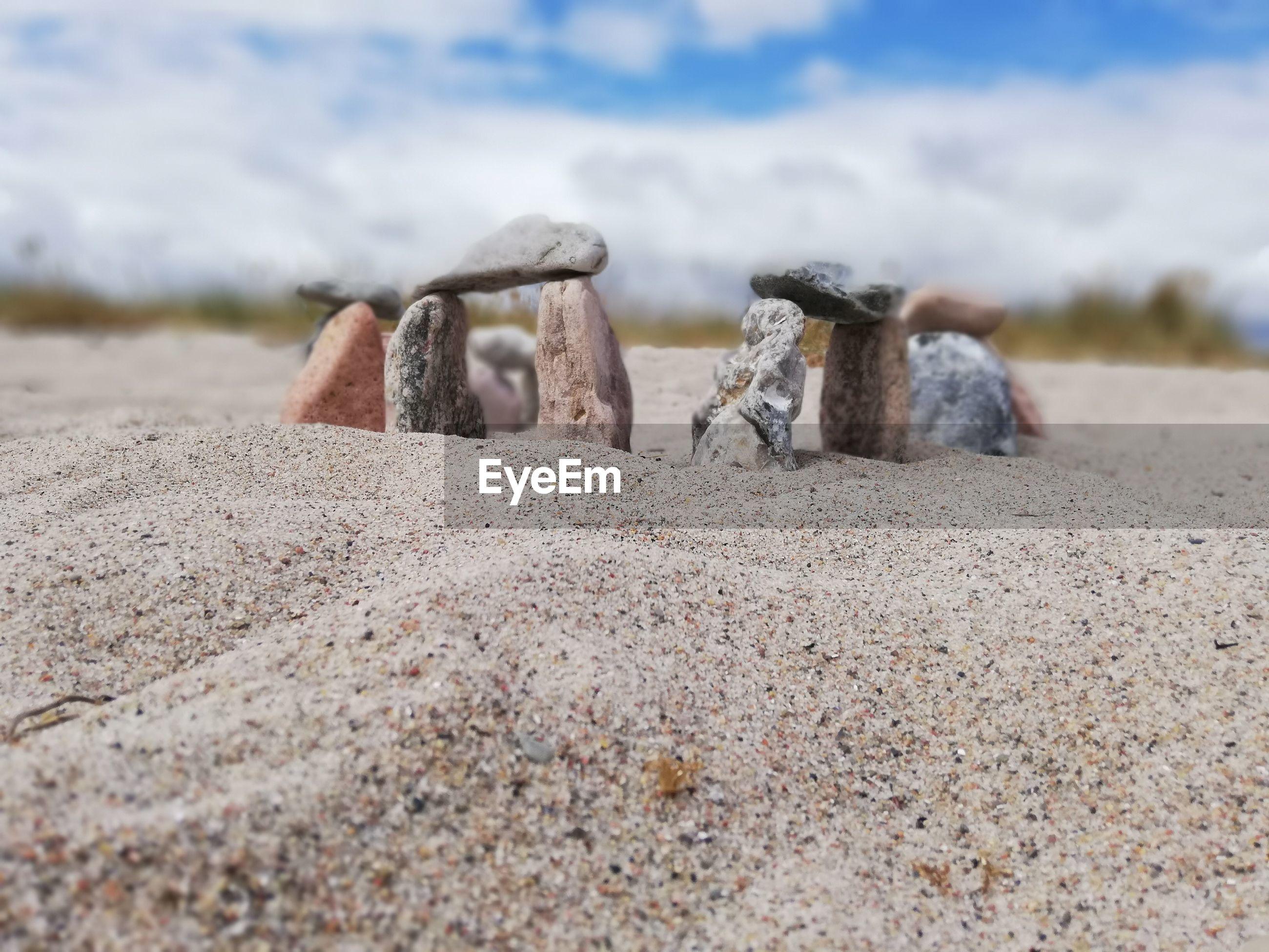 Close-up of miniature stonehenge on a beach