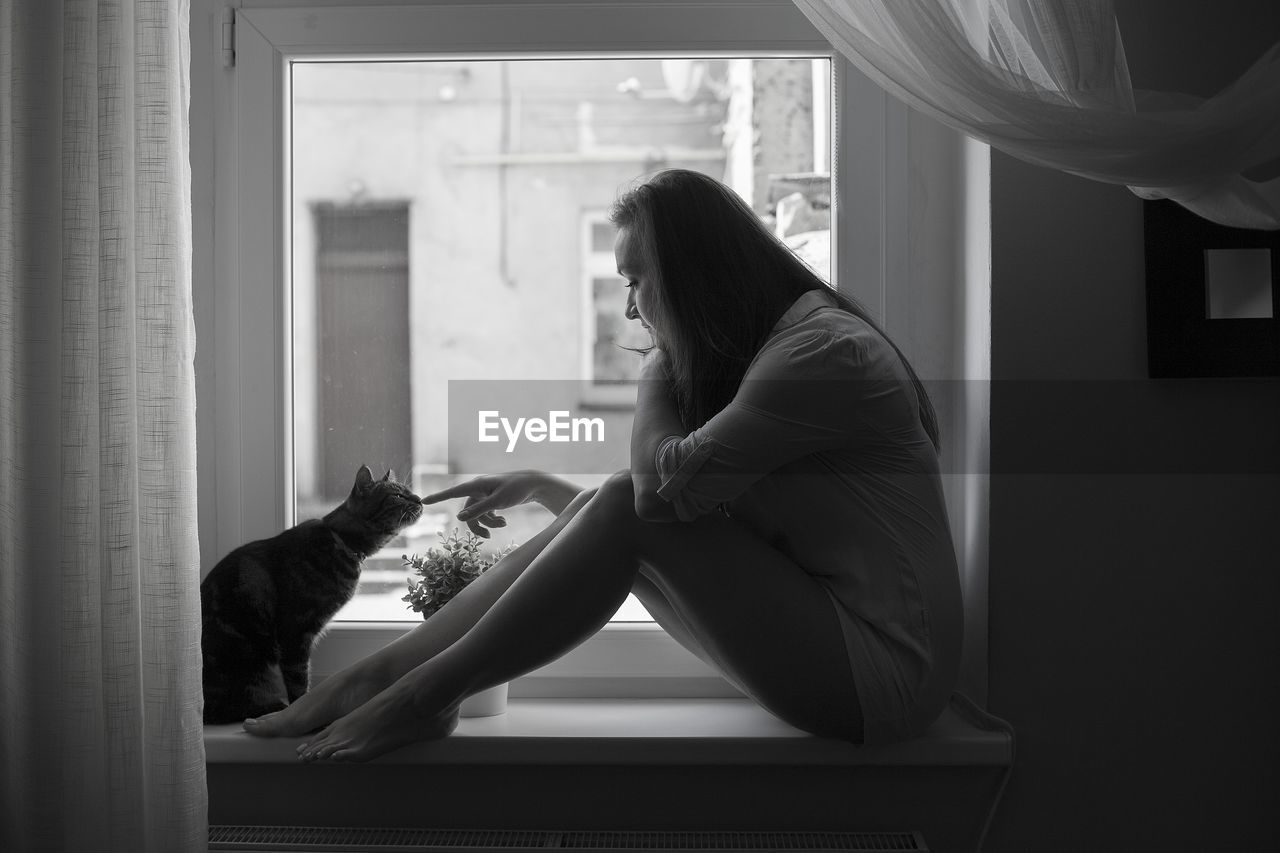 Side view of woman touching cat while sitting on window sill