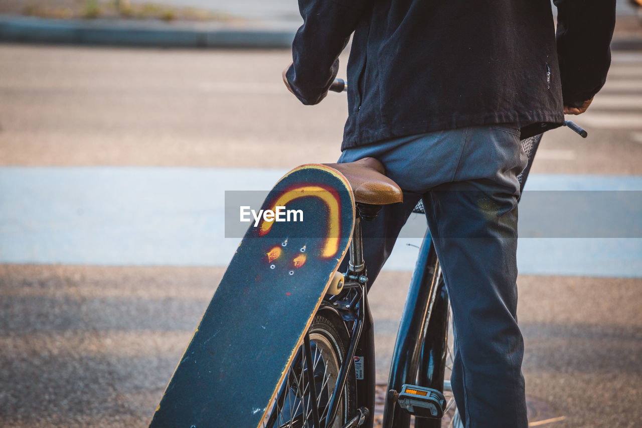 Midsection of man with skateboard on bicycle